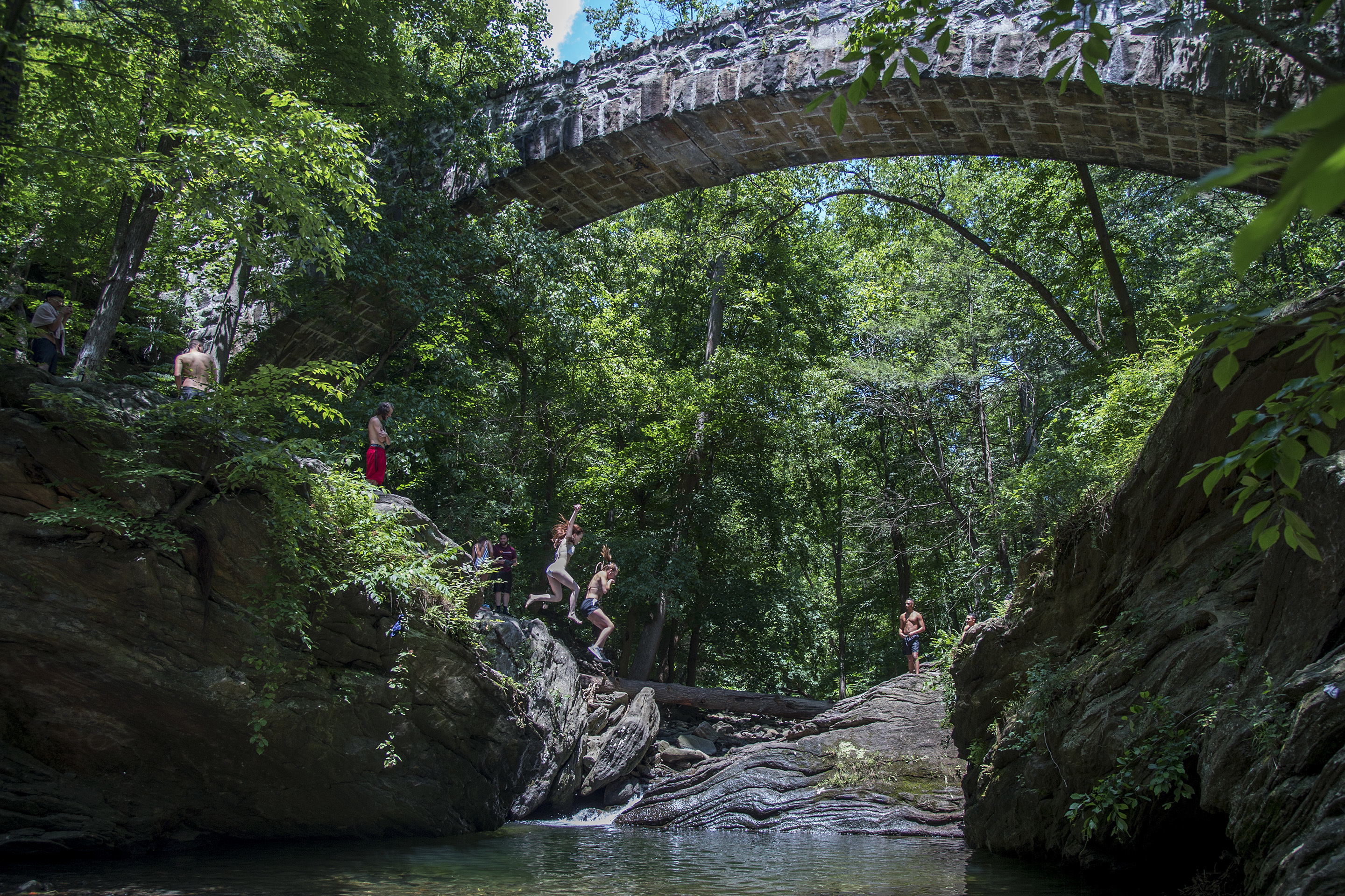 Two girls jump off the rocks at Devil's Pool in the middle of the Wissahickon creek June 28, 2017. Area residents say the foot traffic has gotten out of control and some are calling for the 15-foot watering hole to be filled in with rocks. Complaints include: out of town cards parked on lawns, trash and people urinating on their property. CLEM MURRAY / Staff Photographer
