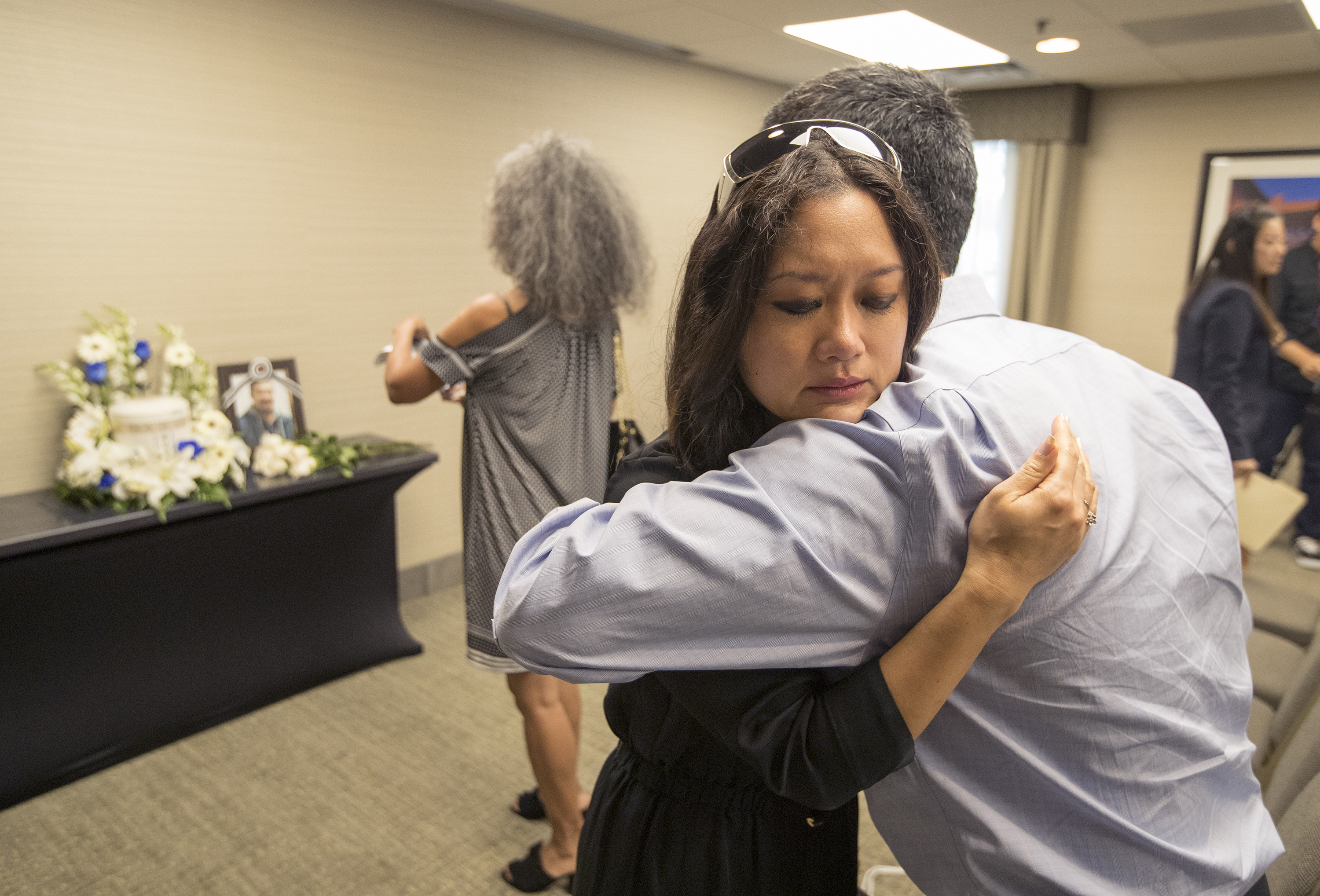 Judi Rhee Alloway, center, hugs Michael Martin, president of AKA (Also Known As), following services for Phillip Clay. Clay´s cremated remains (in background) were returned to Philadelphia, fellow Korean adoptees and friends held a memorial service in 2017.