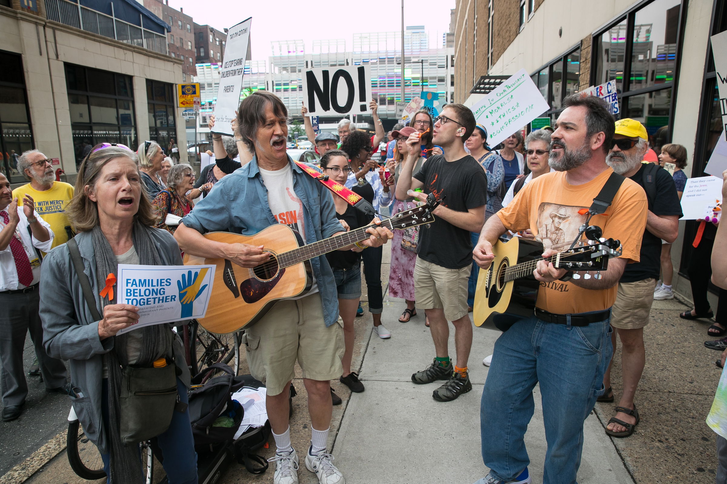 "Janet Ries Stern, left, Bruce Pollack-Johnson, center, and David Heitler-Klevans, right, perform with Voices Rising Philly, at a protest that was art of a ""national day of action"" against the Trump administration´s separation of migrant children and parents. The protest took place outside the offices of ICE, at 8th and Cherry Streets, in Philadelphia."
