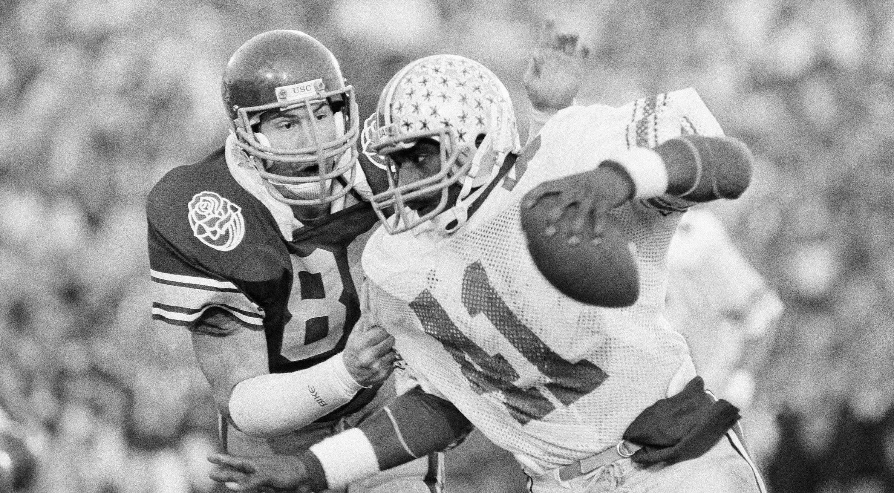 Ohio State tailback Keith Byars getting tackled by USC linebacker Duane Bickett (80) during the Rose Bowl in January 1985.