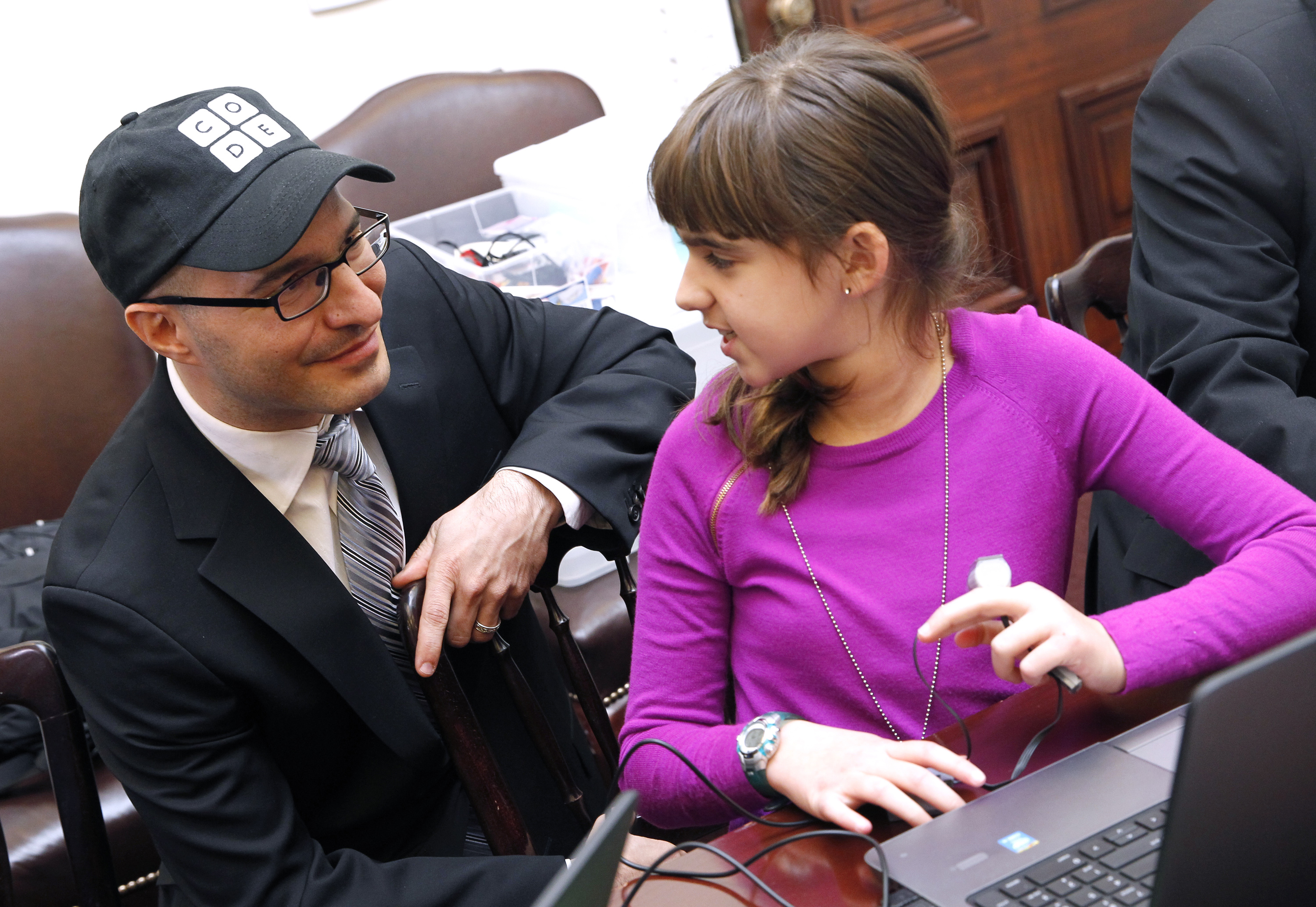 A middle school student shows off her work to Code.org Founder Hadi Partovi at the White House during a coding session in 2014.