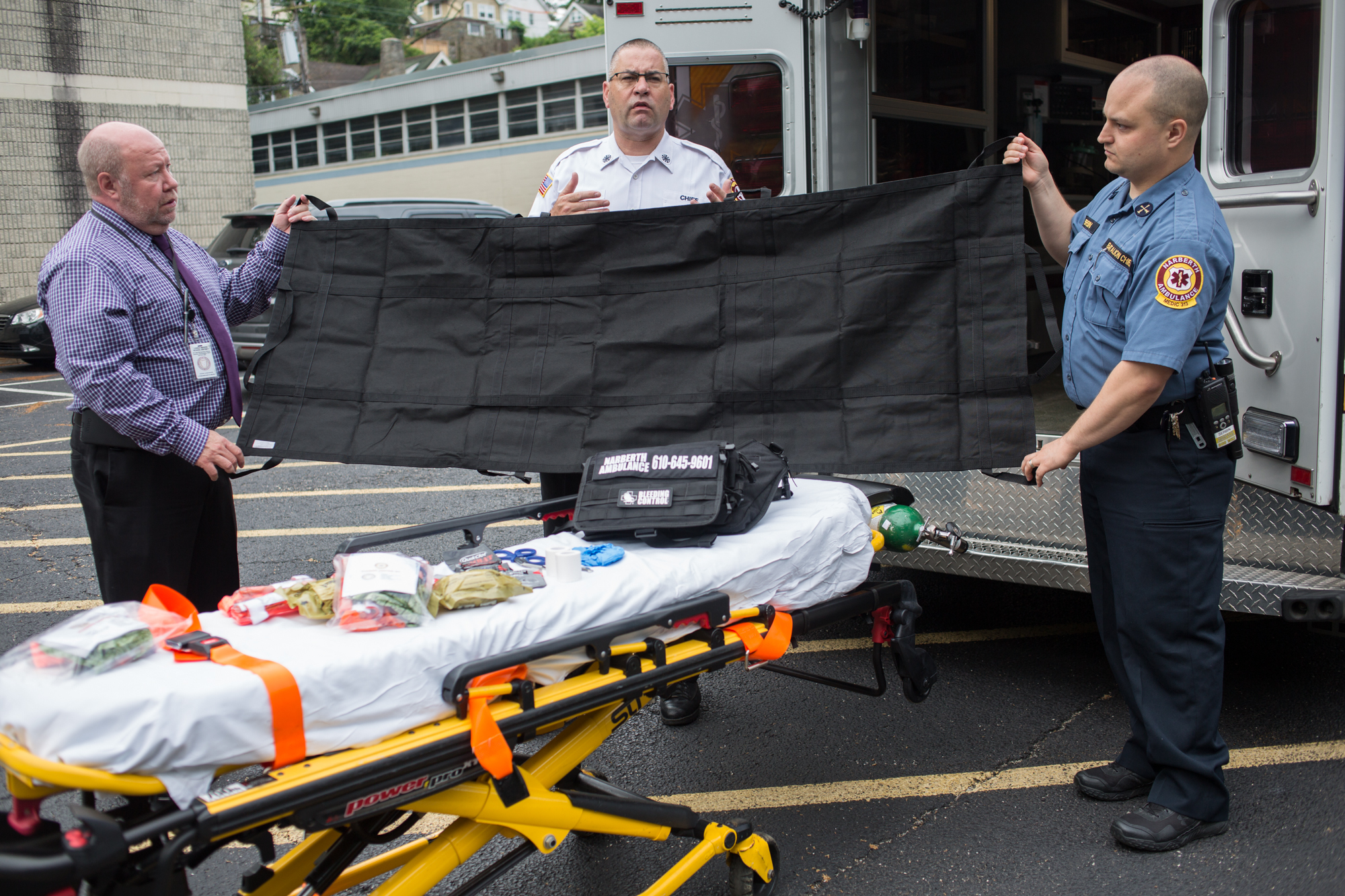 Christopher Flanagan, chief of Narberth Ambulance Company (center), holds up the foldable stretcher included in the trauma kit with assistance from Dennis Witt (left) and Jonathan Serbin.