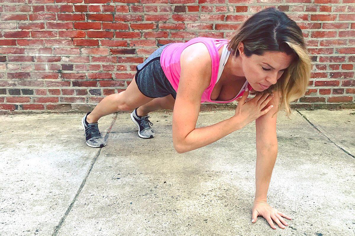 Ashley Greenblatt demonstrates a plank shoulder tap.