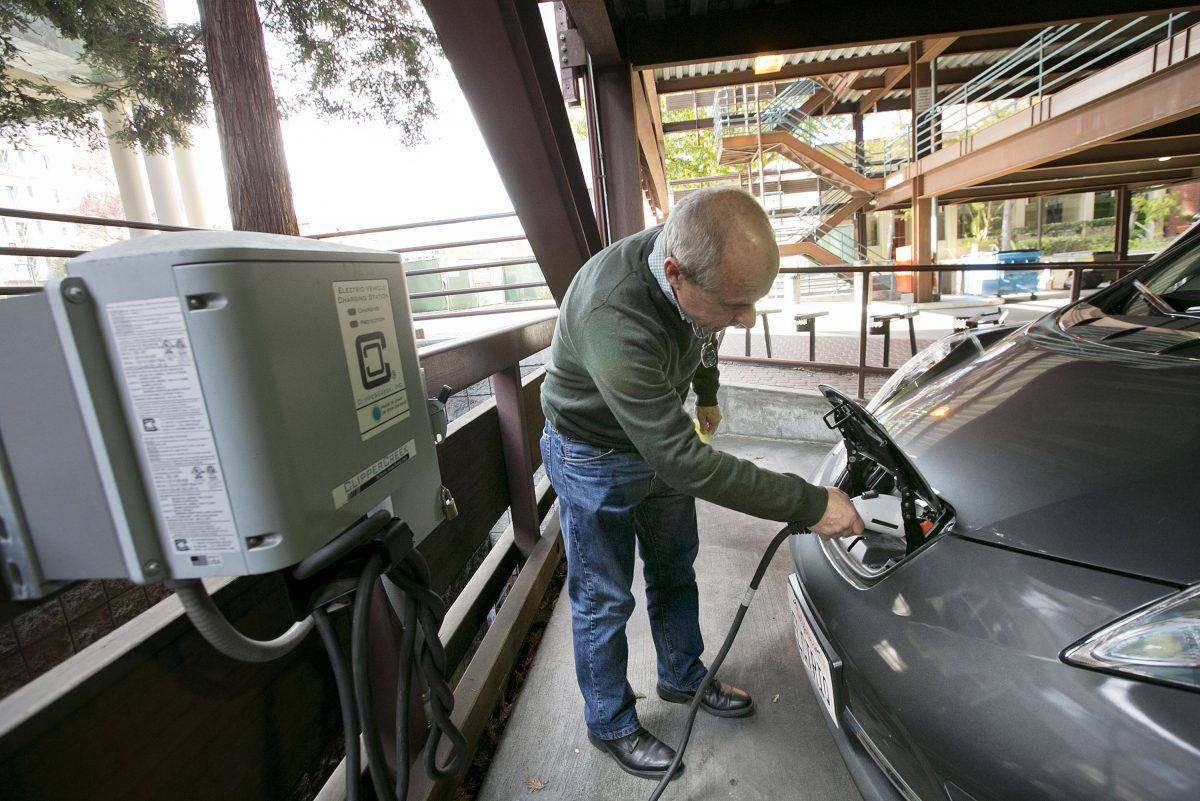 A Nissan Leaf electric car is charged at an EV  station in the public garage in Palo Alto, Calif.