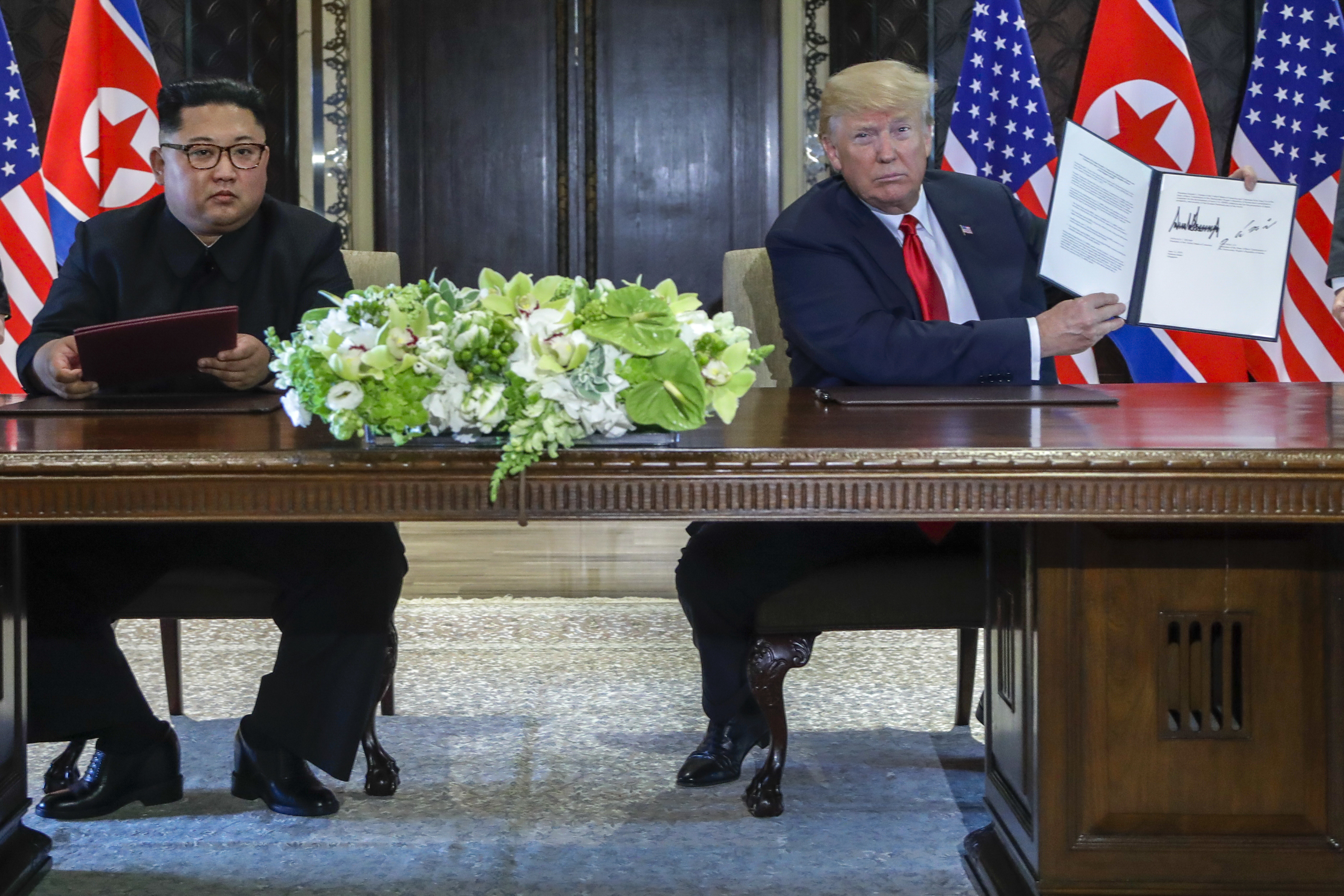 U.S. President Donald Trump holds up the document that he and North Korea leader Kim Jong Un signed at the Capella resort on Sentosa Island Tuesday, June 12, 2018 in Singapore.