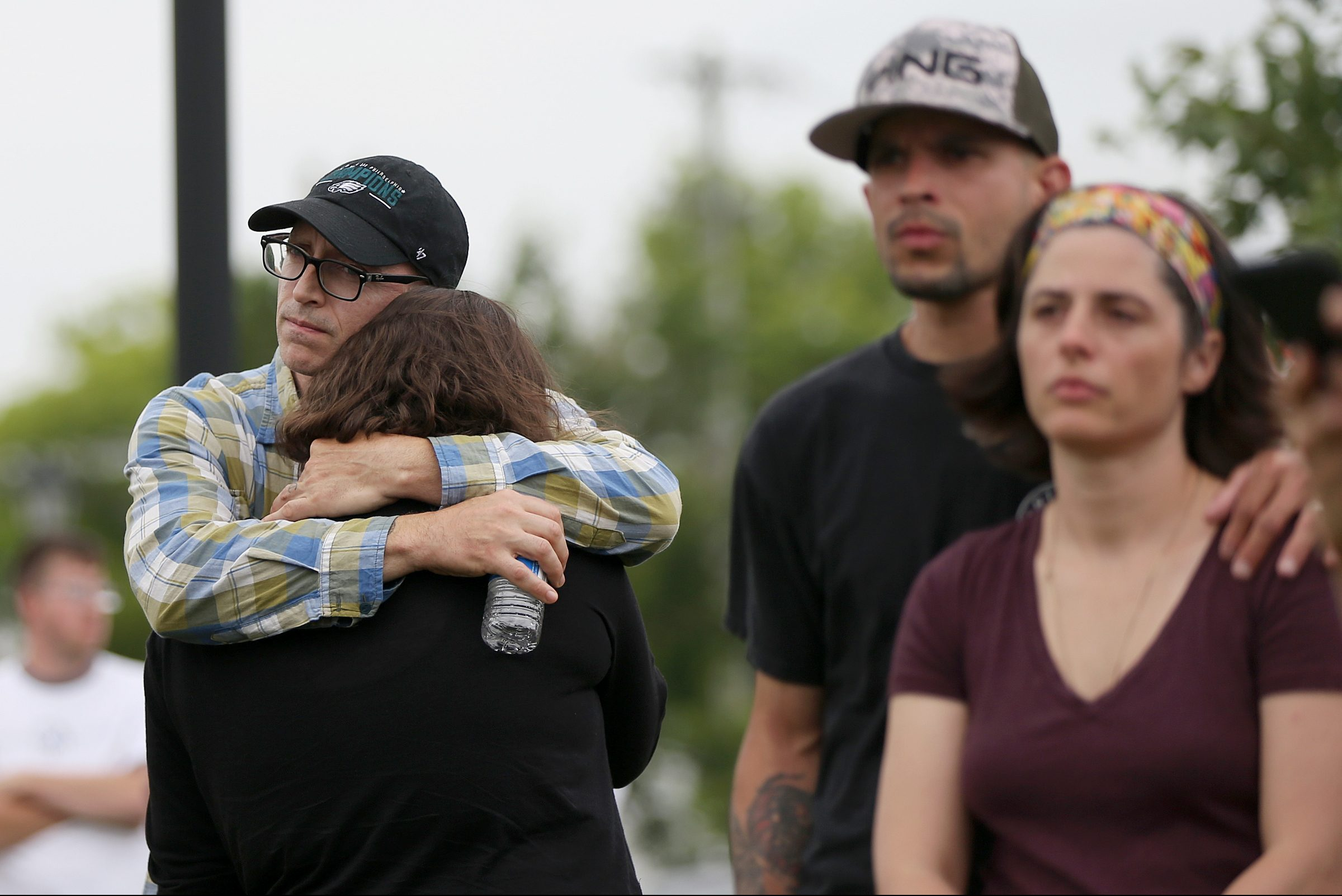 Family members and friends of a man trapped in an underground chamber and presumed dead after an explosion Tuesday rocked a gas station in Bensalem, Pa., listen during a news conference by township public safety director Frederick Harran on Wednesday, June 13, 2018. The explosion also left one person in critical condition.