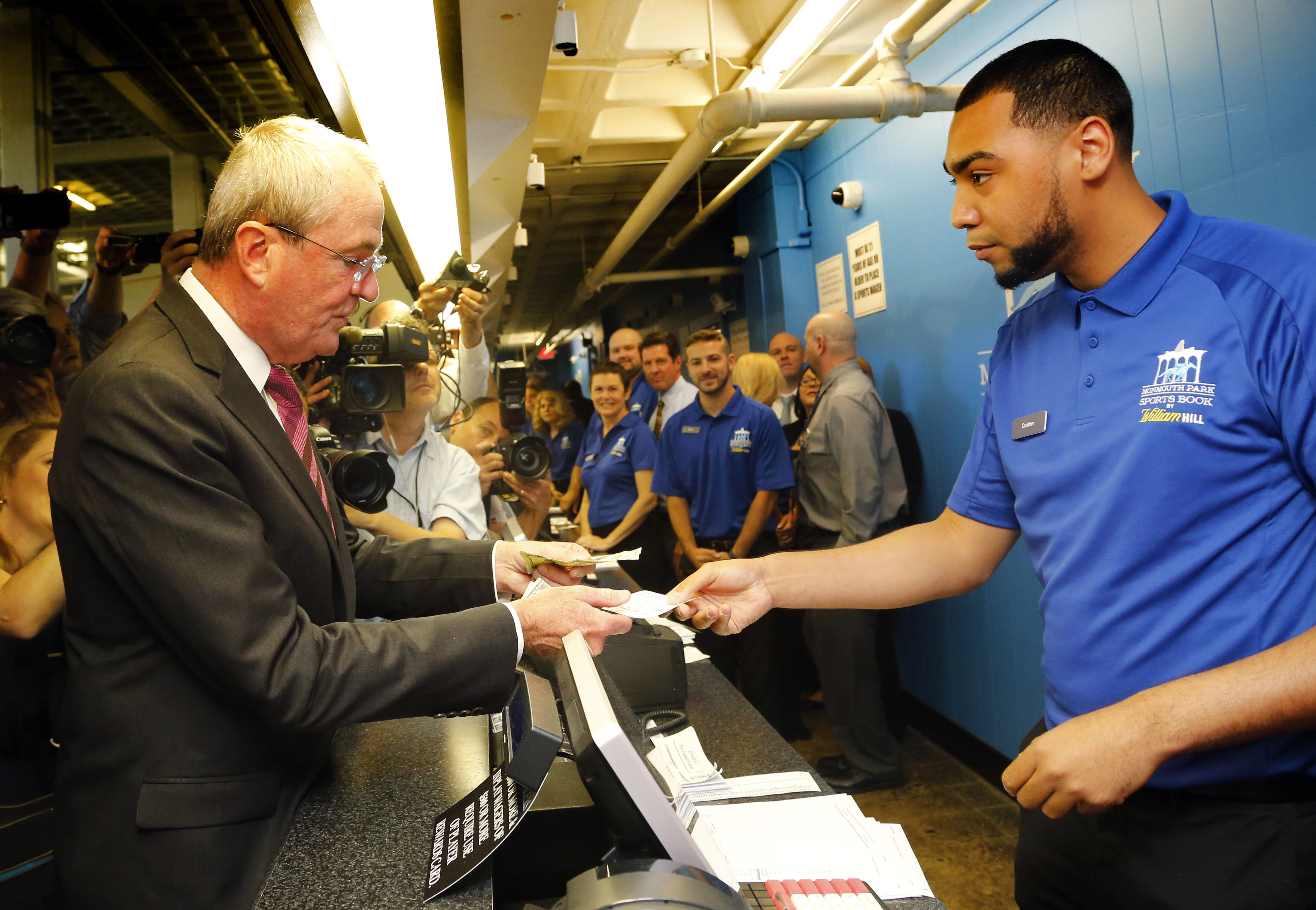 New Jersey Governor Phil Murphy, makes the first wager with Monmouth Park Sports Book ticket writer Quentin Harris.