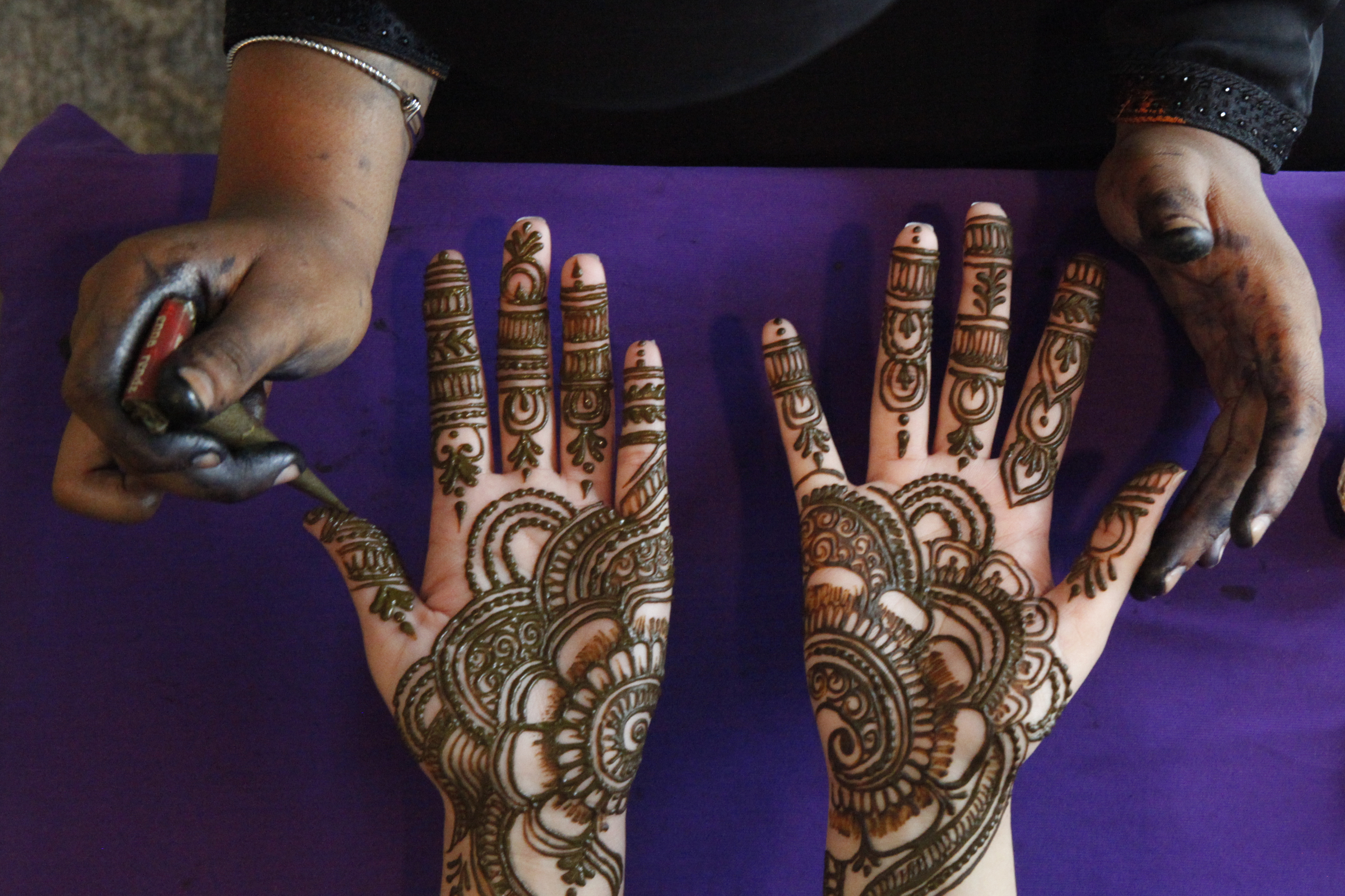 Muslim women get designs drawn on their hands in henna in preparation for Eid al-Fitr, a celebration at the end of Ramadan. This is an important religious holiday for the community.