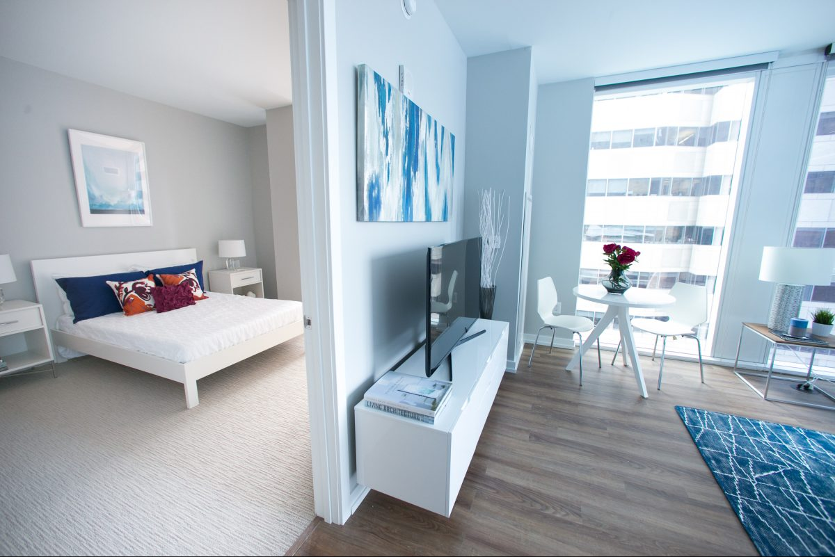 A bedroom and living room in a two bedroom- two bathroom apartment  at 1919 Market St.
