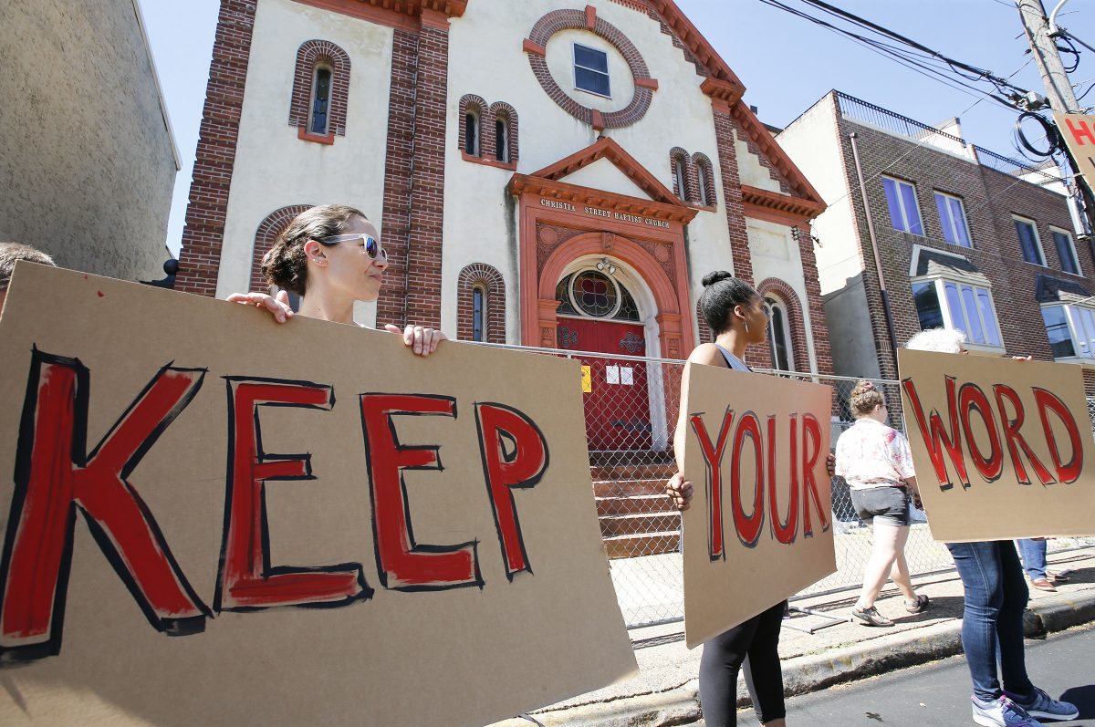 Aliza Schmidt (left), Charlette Caldwell (center) and Joni Lipson hold signs during a last-ditch protest attempt to stop the planned demolition of the Christian Street Baptist Church in the Bella Vista section of South Philadelphia on Saturday. The demolition is planned in the coming weeks.