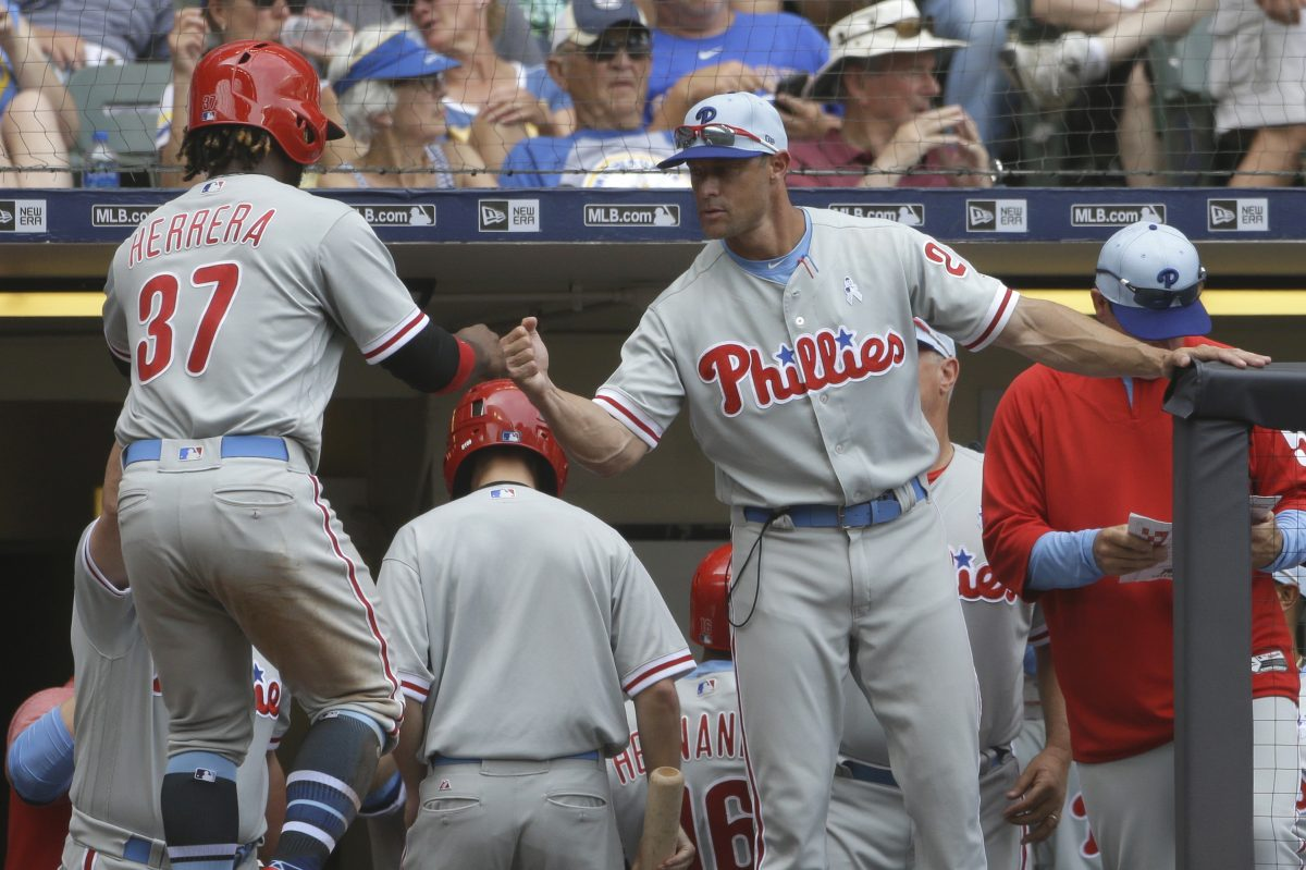 Gabe Kapler congratulates Odubel Herrera after Herrera scored in the seventh inning of the Phillies' 10-9 win over the Brewers on Sunday at Miller Park.