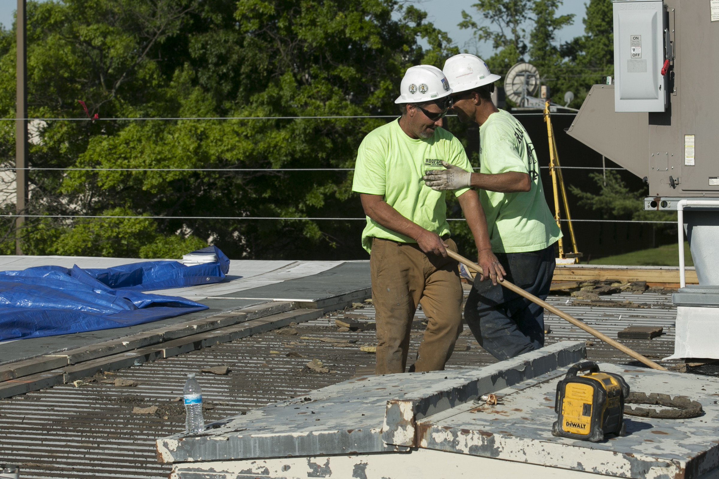 Rich Kinkade (left) and Danny Henry finish a discussion while clearing old roofing off the Bellmawr Post Office in Bellmawr, NJ, on the morning of Thursday, June 14, 2018. Construction company EDA Contractors is training its roofers and carpenters, some of its most masculine workers, how to be emotionally intelligent. MAGGIE LOESCH / Staff Photographer