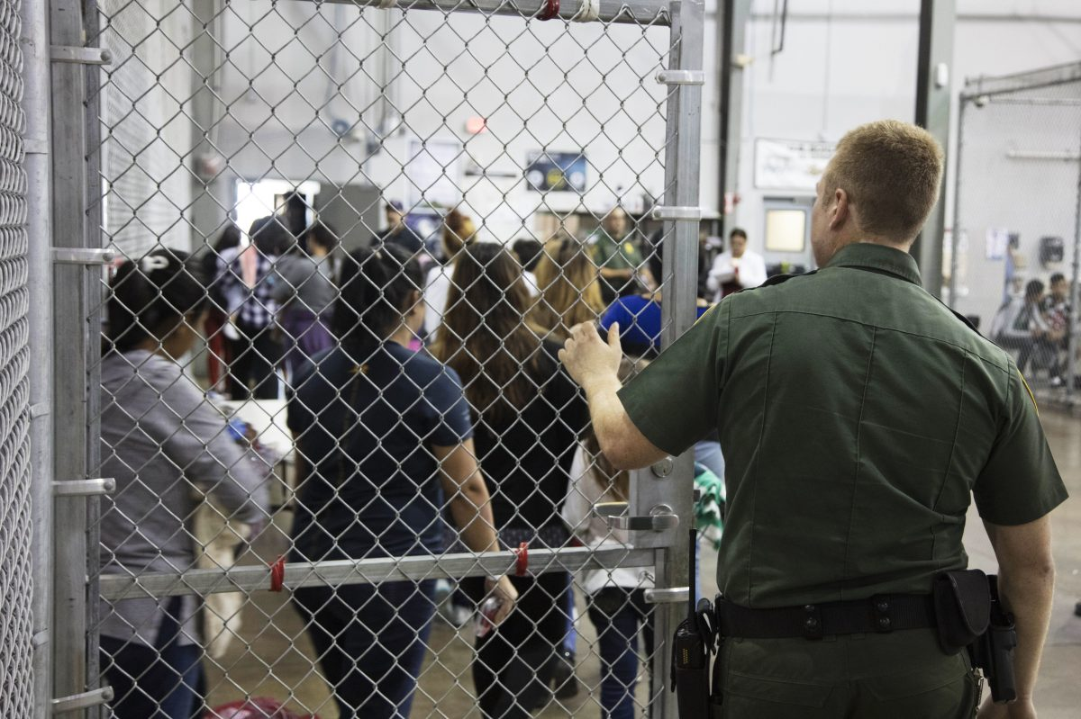 In this photo provided by U.S. Customs and Border Protection, a U.S. Border Patrol agent watches as people who have been taken into custody related to cases of illegal entry into the United States, stand in line at a facility in McAllen, Texas.