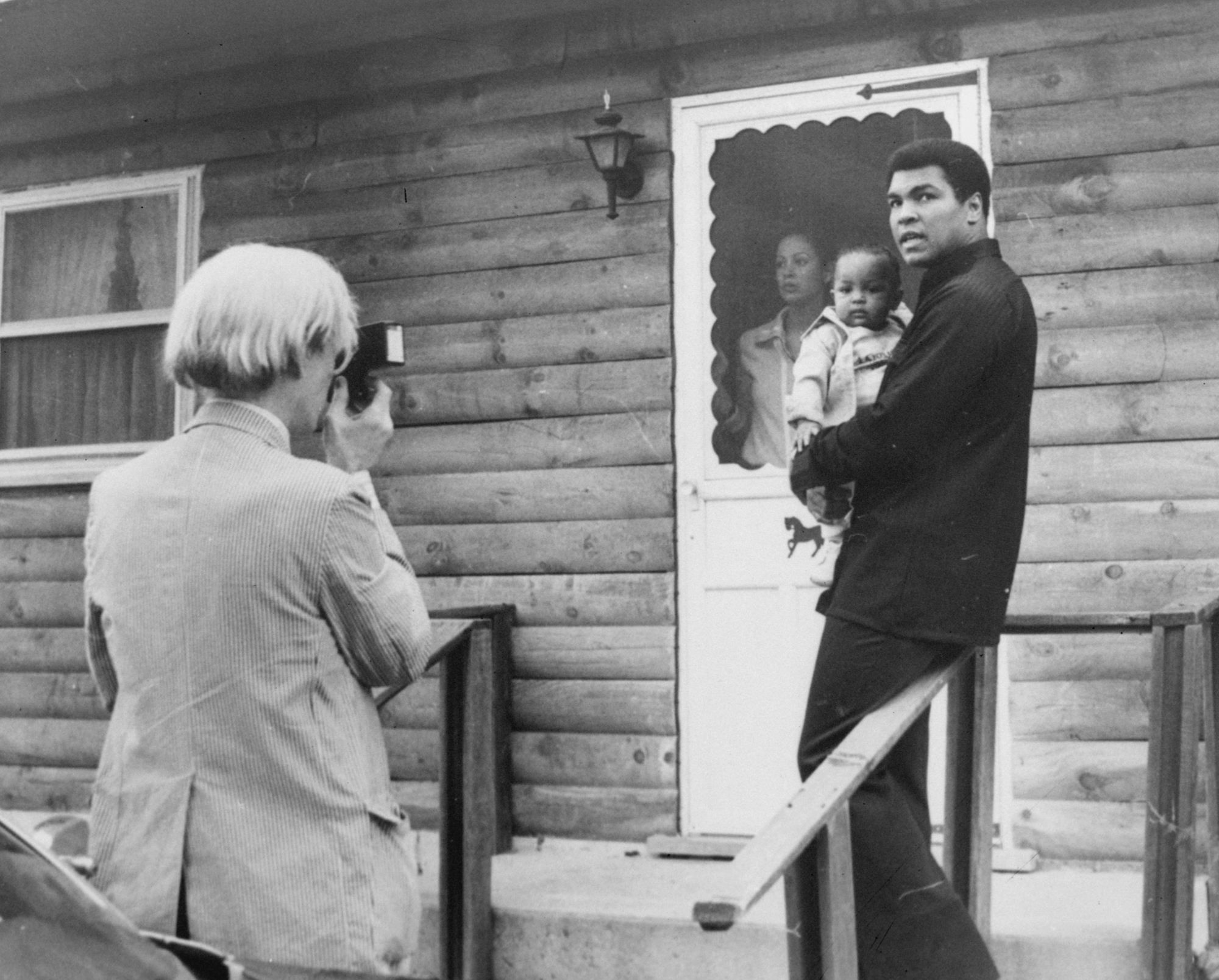 Pop artist Andy Warhol, left, is shown photographing Muhammad Ali, his infant daughter, Hanna, and wife, Veronica, Thursday, August 18, 1977, at Ali´s training camp in Deer Lake, Pa. (AP Photo)