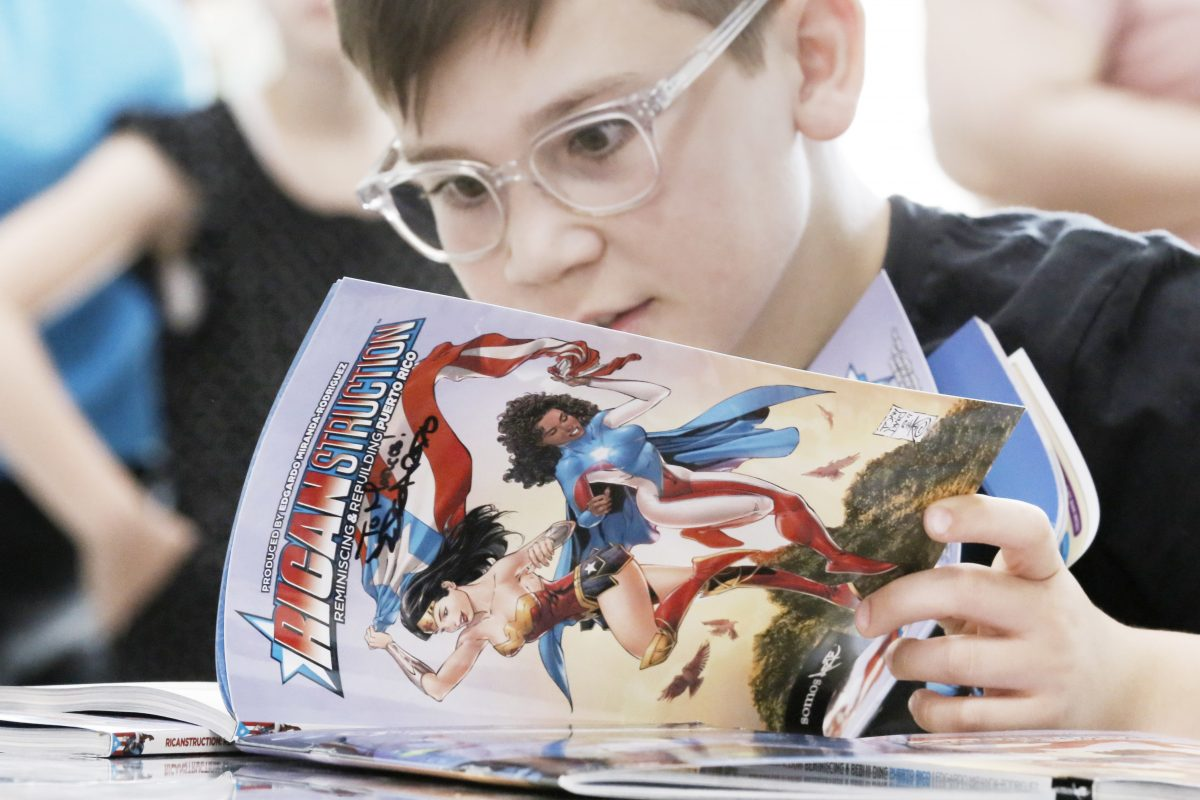 """Lucca Petrecca, 11, of Princeton reads the comic book """"Ricanstruction,"""" which author Edgardo Miranda-Rodriguez just signed at Taller Puertorriqueno in Phila., Pa. on June 16, 2018."""
