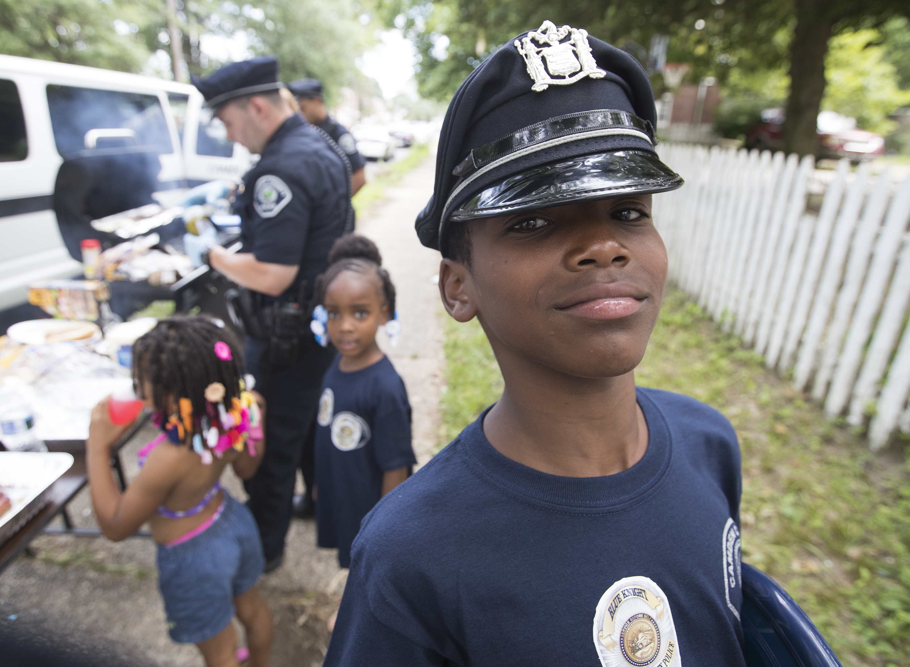 Camden County Police officers grilled hot dogs and hamburgers and gave away T-shirts and stickers in South Camden on Saturday, July 1, 2017. The event  is one of a series of such outreach attempts by the police department to build bonds with the community. Na'zheem Williams, 11, proudly tries on one of the officers´ hats.