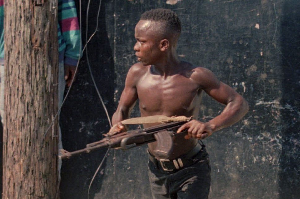 A teenage fighter with the National Patriotic Front of Liberia (NPFL) charges forward in downtown Monrovia, Liberia, on May 10, 1996.