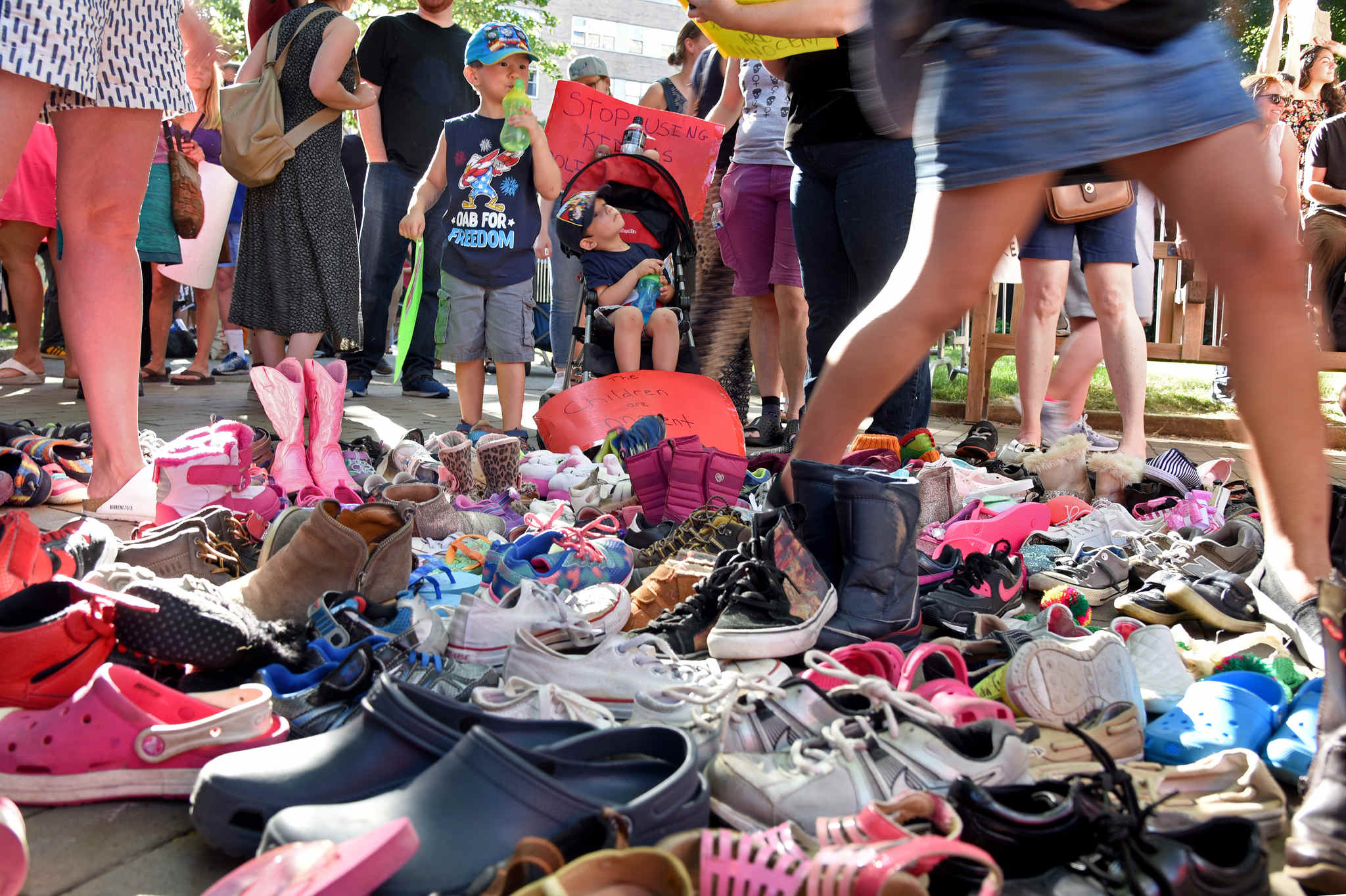 Ethan Schiller (left), 4, and his brother Lukas, 2-1/2, look over the dozens of shoes representing children who were separated from their parents by immigration officials, part of a protest at Rittenhouse Square on Tuesday, near the hotel hosting a GOP fundraiser with Vice President Pence.