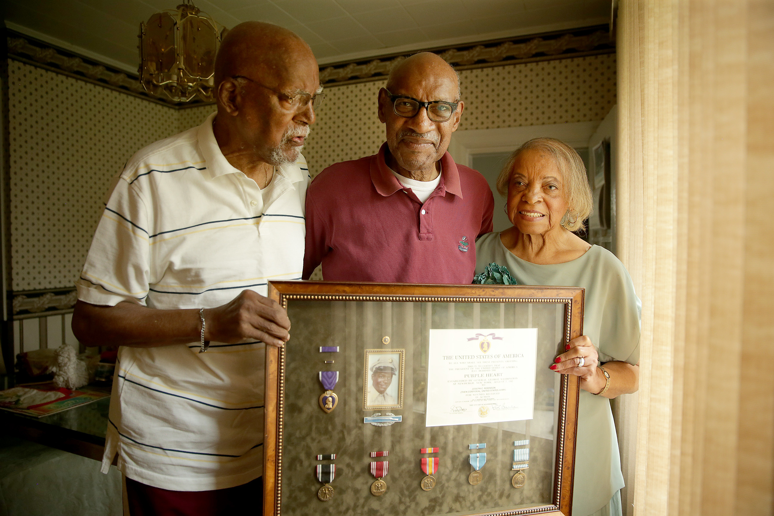 Harry Robinson (left), 86, Wallace Robinson (center), 81, and Mary White, 84, hold up a tribute to their brother Joseph Robinson. Cpl. Joseph Robinson died a prisoner of war in North Korea in 1951.