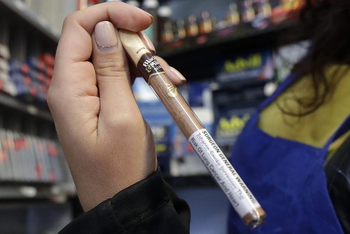 In this May 17, 2018 photo, Miriam Zouzounis holds a Black & Mild Wine cigarillo while interviewed at Ted´s Market, her family´s store, in San Francisco.