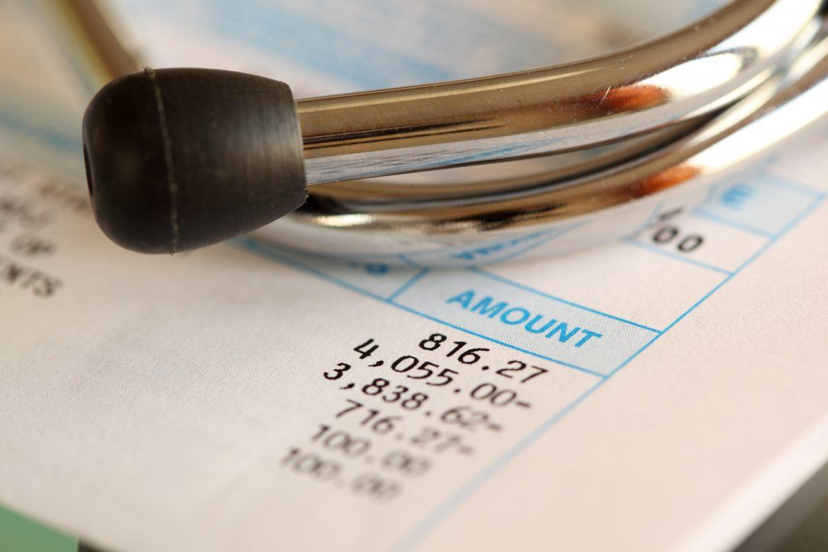 studio shot of medical bill and stethoscope