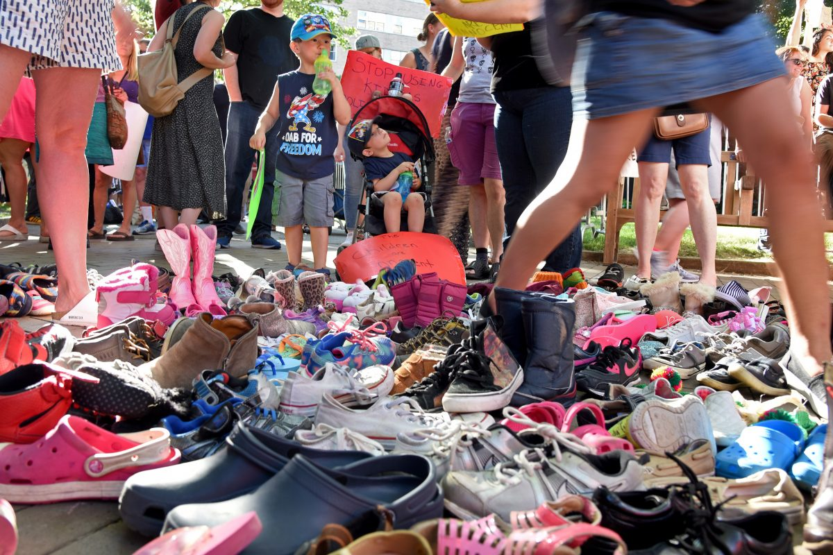 Ethan Schiller (left), 4, and his brother Lukas Schiller (right), 2-1/2, look over the dozens of shoes representing children who were separated from their parents by immigration officials, during a protest outside the Rittenhouse Hotel June 19, 2018, where Vice President Pence attended a fund-raiser for GOP gubernatorial nominee Scott Wagner.