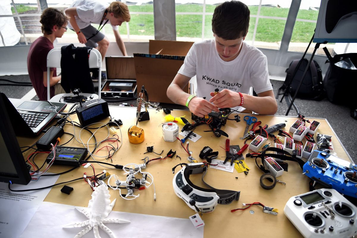 At Philly's first Maker Faire, Kevin Fallon (at table), Sam Weissman (rear, left) and Nolan Gelinas (rear, right) work on their drones as part of the Kwad Squad, a group of high school classmates and family friends formed to pursue their passion.
