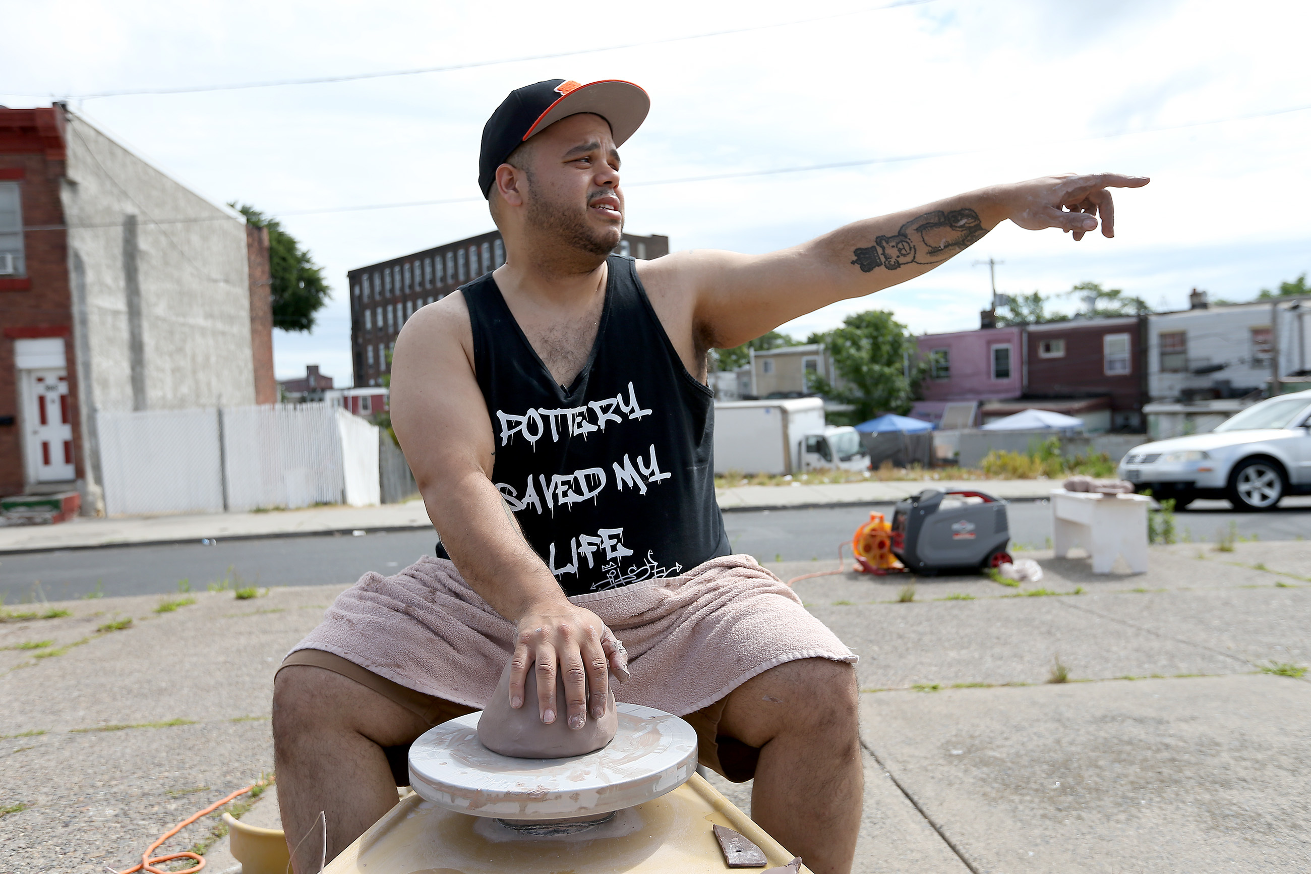 Award-winning ceramic artist Roberto Lugo points to an area where he use to graffiti as he does a pottery demonstration at E. Tusculum and Somerset streets in Philadelphia, PA on June 19, 2018.