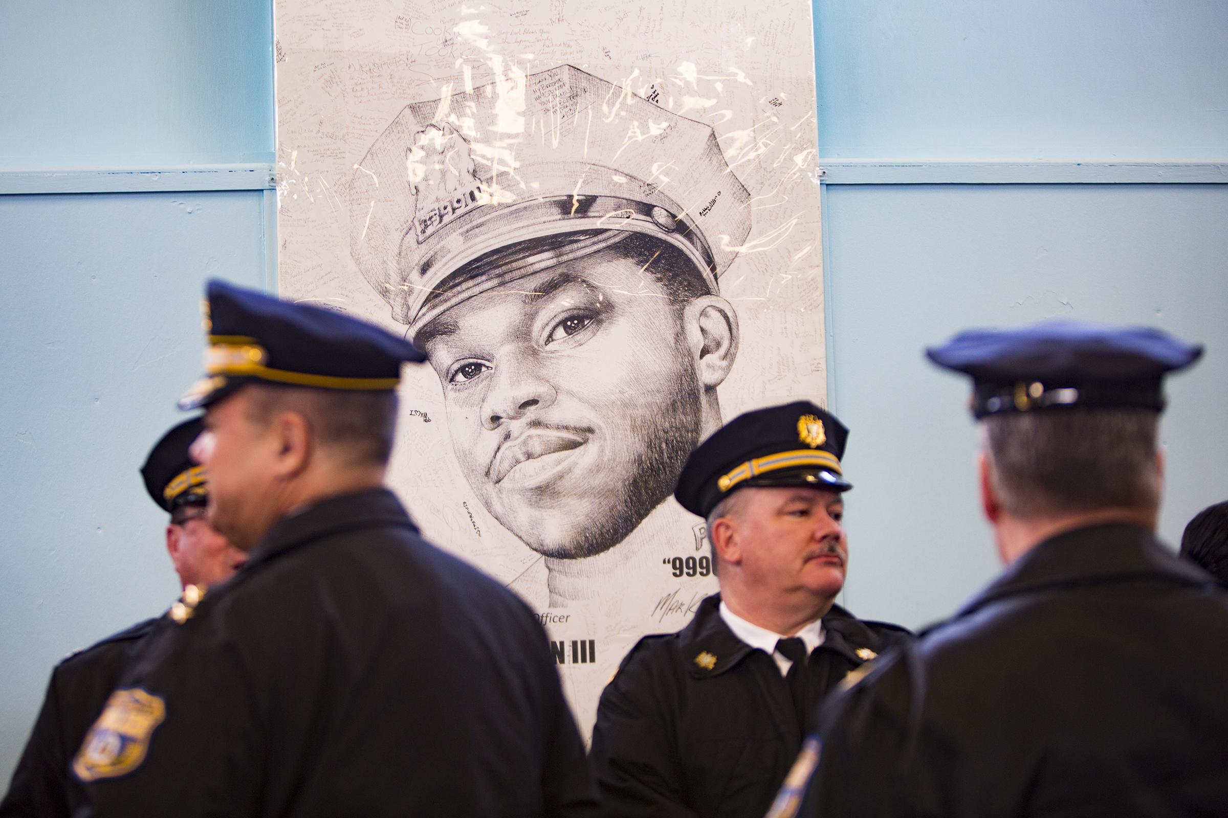 A portrait of officer Robert Wilson III looks over officers gathered in his honor at the 22nd district on the 3rd anniversary of his death.