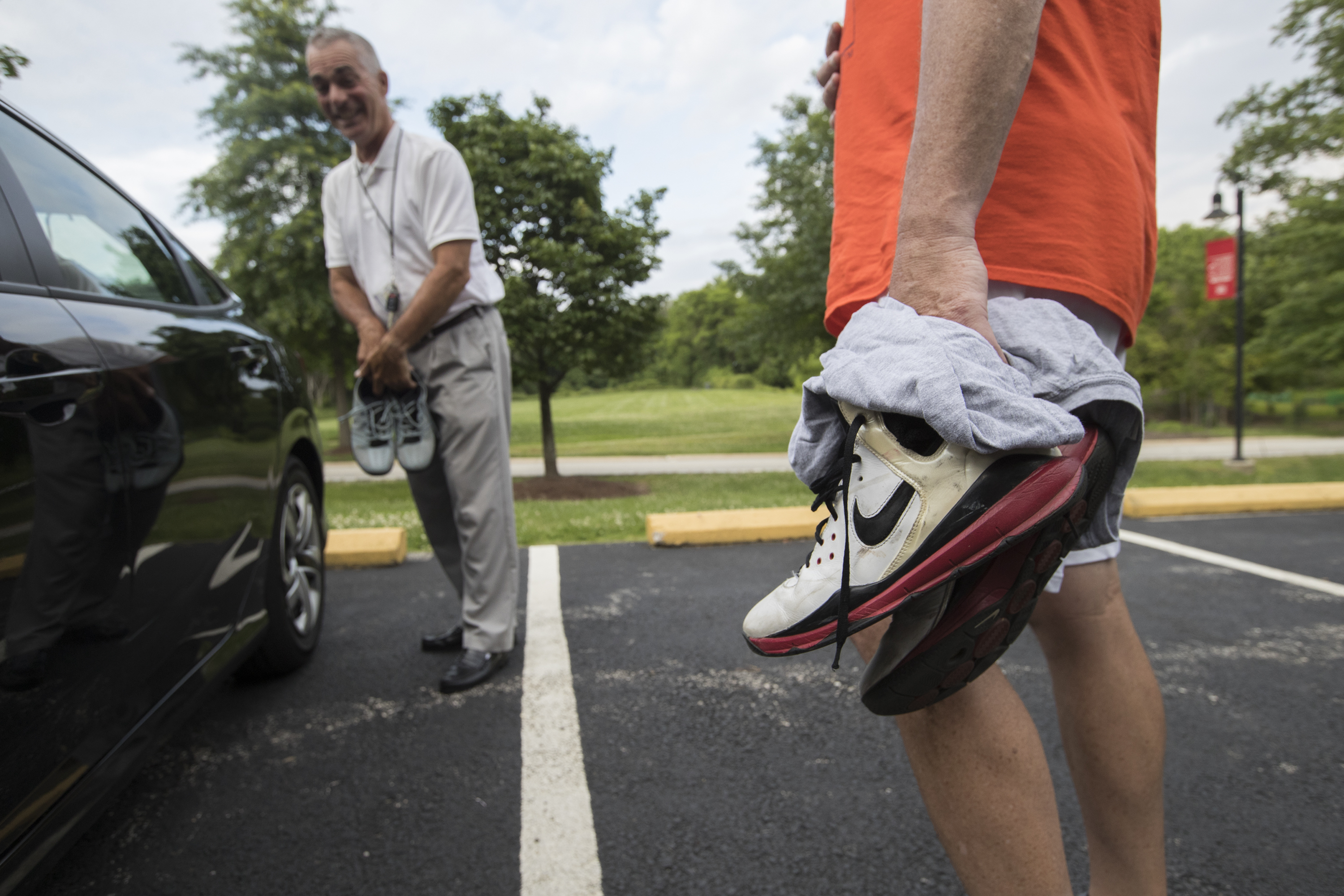 This group of players have been playing pickup basketball games for over 35 years. Rich Blasetti, left, and Geoff Deasey get out of their cars with sneakers in hand on June 20, 2018.