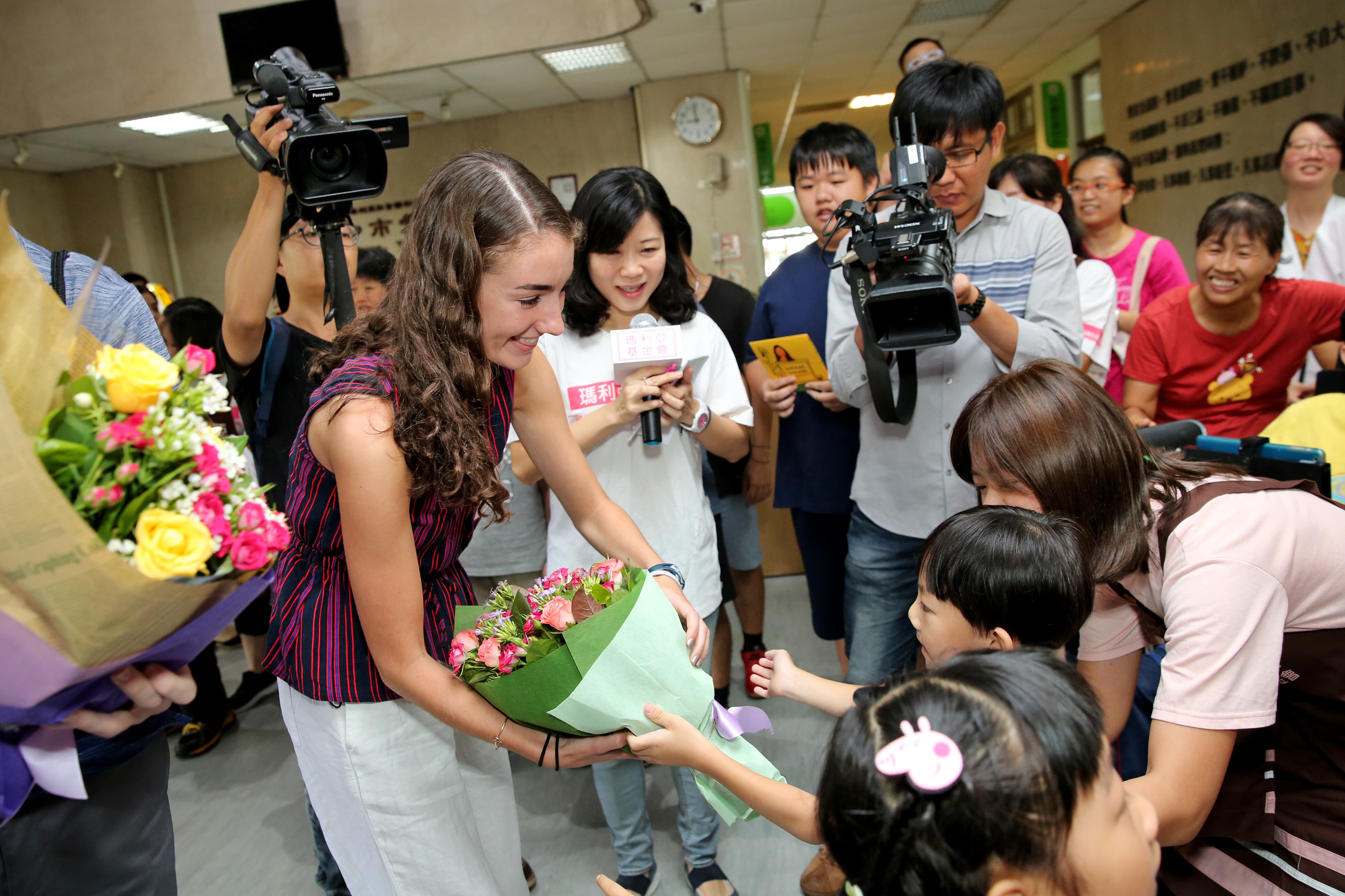 Katherine Commale, 17, is given flowers as she arrives at the Maria Social Welfare Foundation in Taiwan June 13, 2018. Commale and her family just returned from the trip to Taiwan where she gave a TED-type talk and met the president. DO not credit TOM GRALISH / Staff Photographer Credit: Maria Social Welfare Foundation of Taiwan