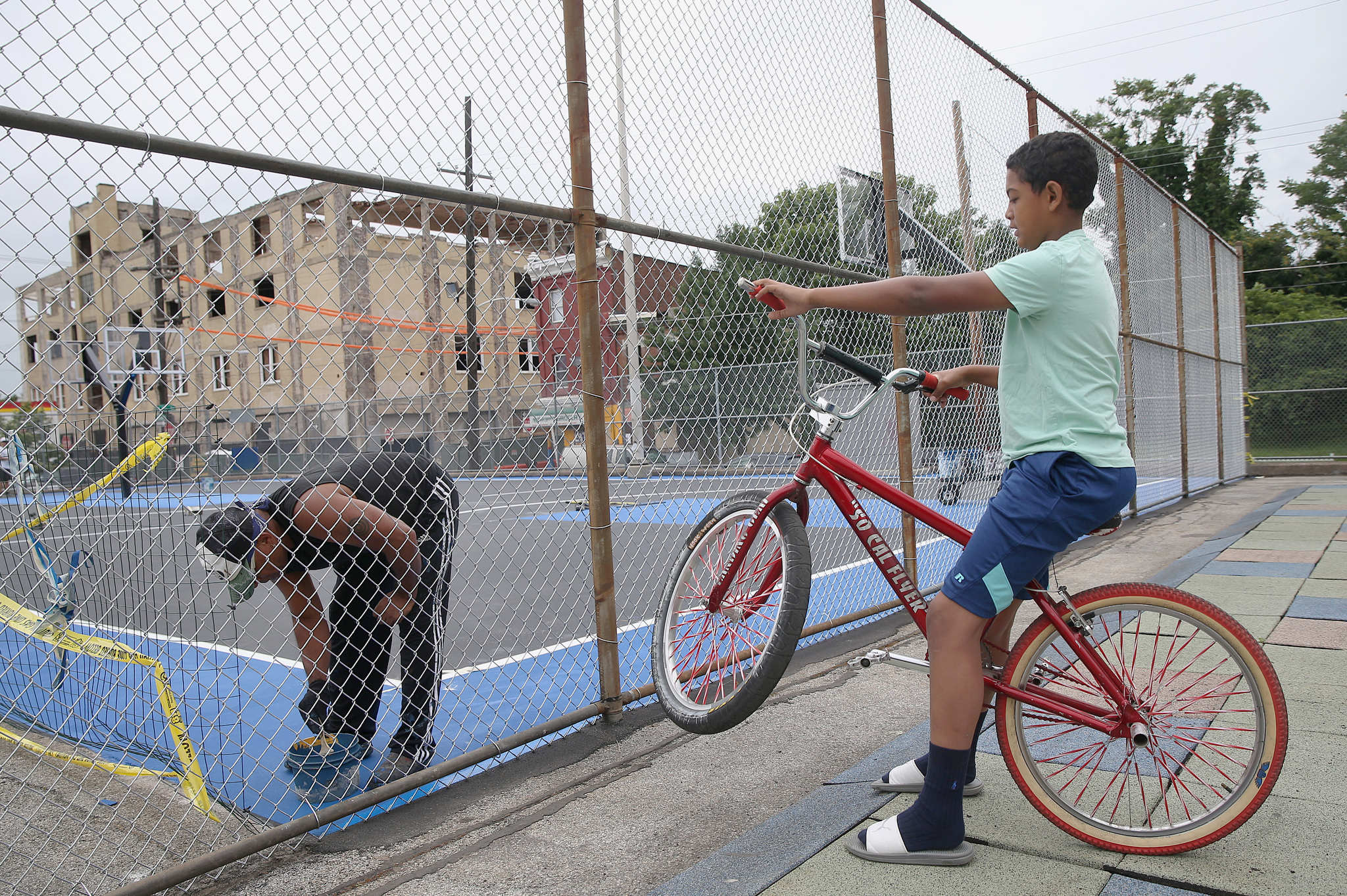 Troy Walker, 11, right, who attends the adjacent John F. Hartranft School Elementary School, speaks with Cass Construction worker Jack Wilmore as he paints the newly renovated basketball court at the playground at Eighth and Cumberland streets in North Philadelphia.