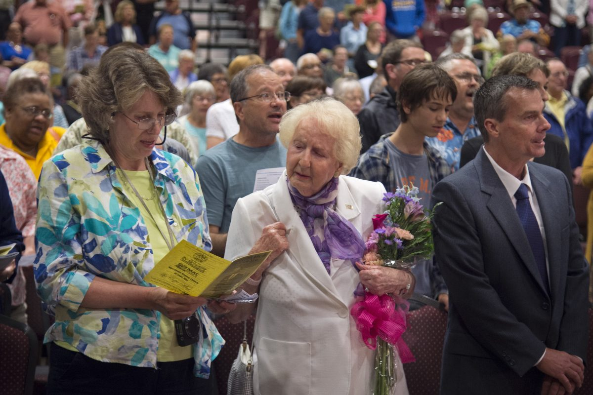 """Anna Wright (center), 89, of Newtown Square, who was in attendance 60 years earlier when Martin Luther King Jr. addressed a convention of Quakers in Cape May, stands to join in singing """"America the Beautiful"""" at the conclusion of the city's commemoration of the anniversary June 27, 2018. With her are her daughter Lisa Lister and nephew James TerBush."""