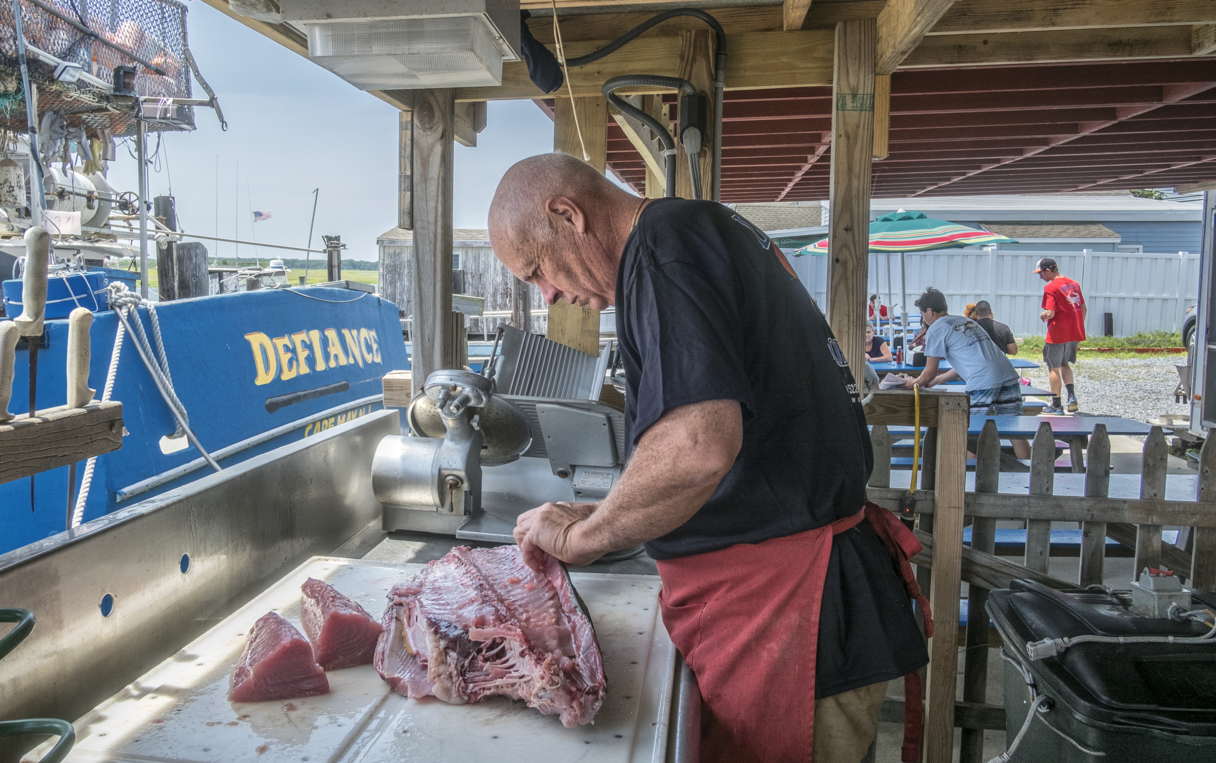 Bill Bright , owner and fisherman, butchers a fresh tuna at his family run restaurant Hooked Up Seafood.