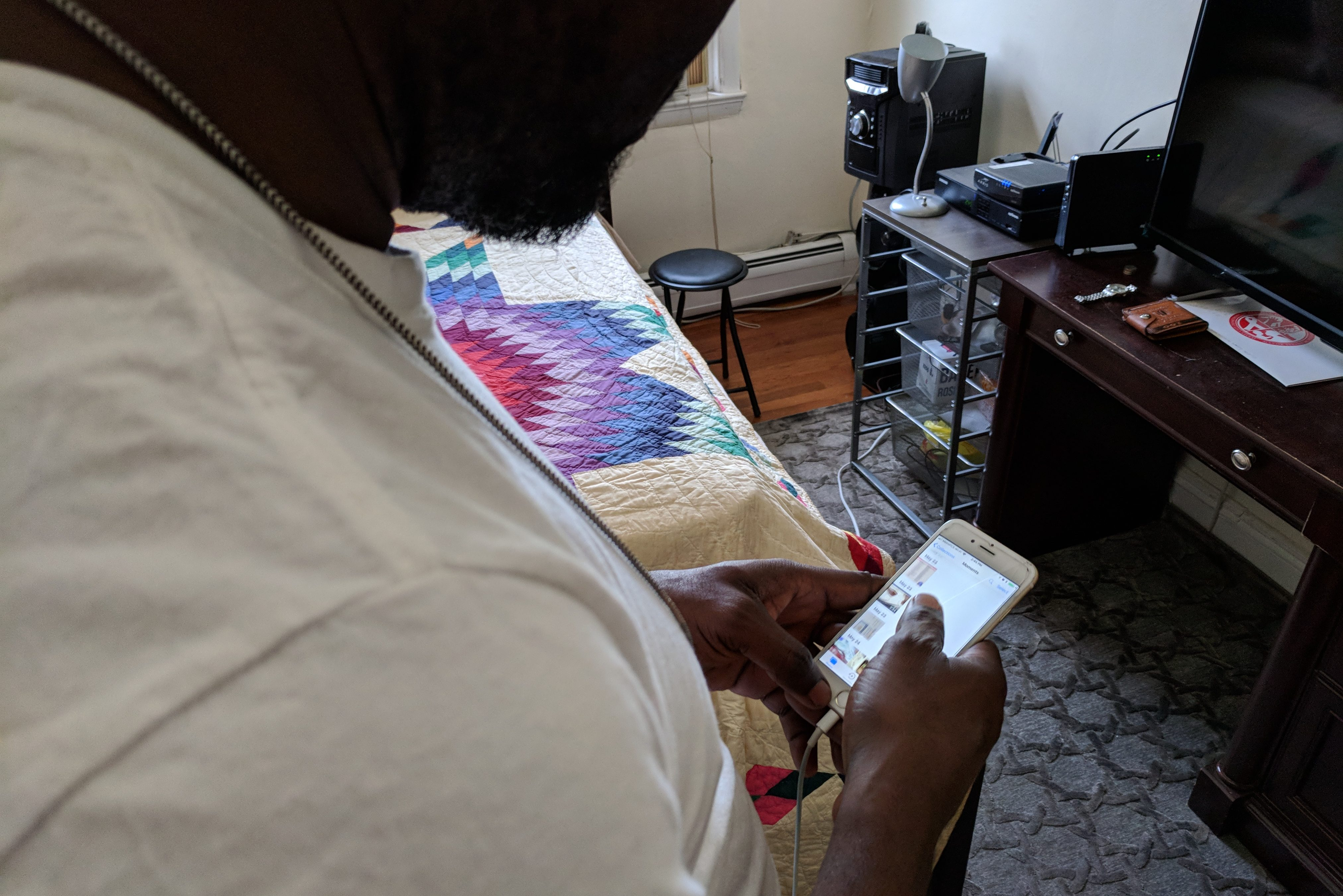 Taiwo Saka looks through photos on his phone of his friends and family back home in Nigeria.