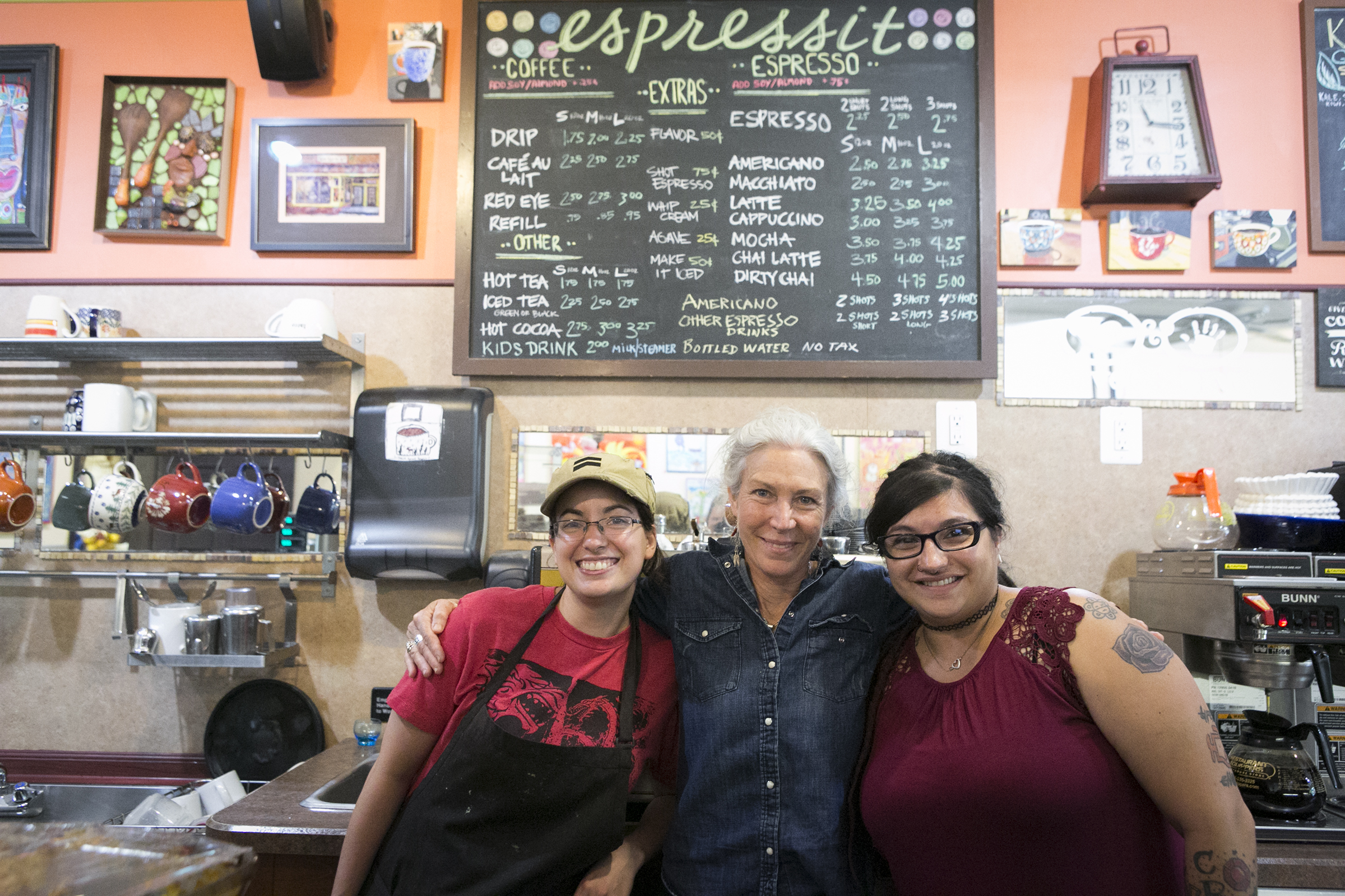 Owner Stacey Douglas (center) and managers Kim Mikhail and Kat Agront stand at the counter at Espressit Coffee, a community gathering spot on Haddon Avenue in Westmont, NJ. After 10 years in business, Douglas plans to sell the shop.