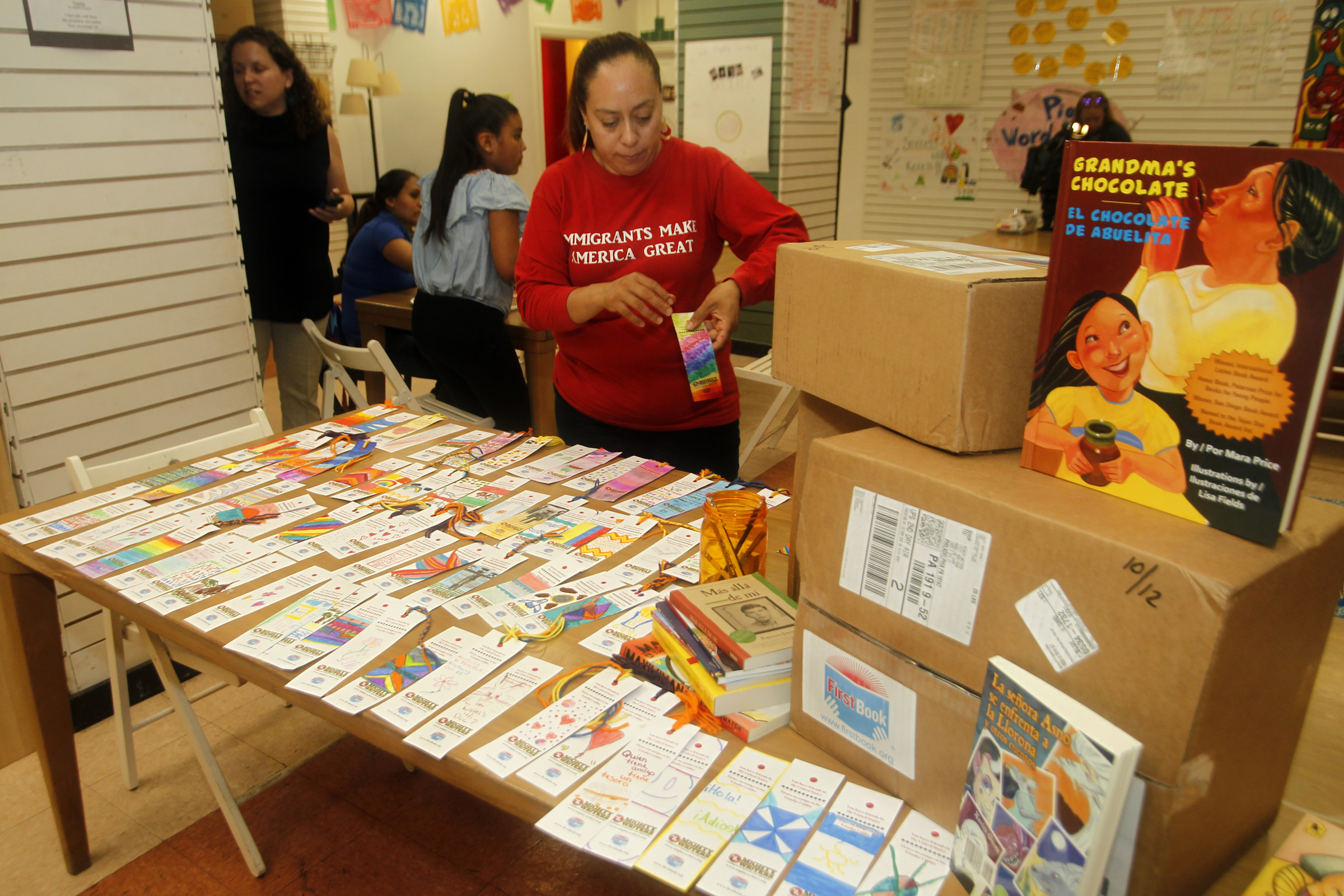 Alma Romero looks over the books and bookmarks going the Berks County detention center at Mighty Writers´ El Futuro location in the Italian Market on Thursday, June 28.