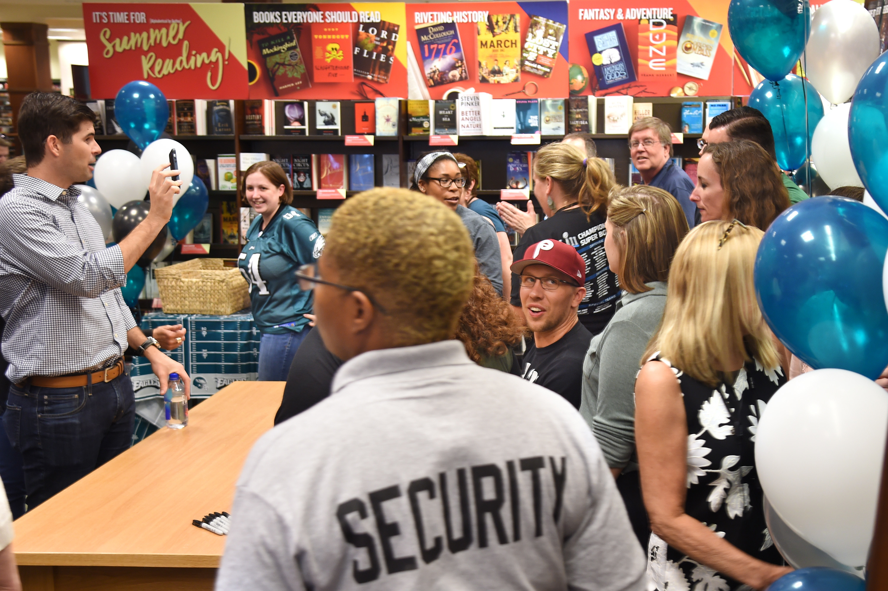 """""""Believe It"""" co-author Nick Foles (in Phillies cap) is surrounded by bookstore employees after he finished autographing books at the Barnes & Noble in Devon June 28, 2018. TOM GRALISH / Staff Photographer"""