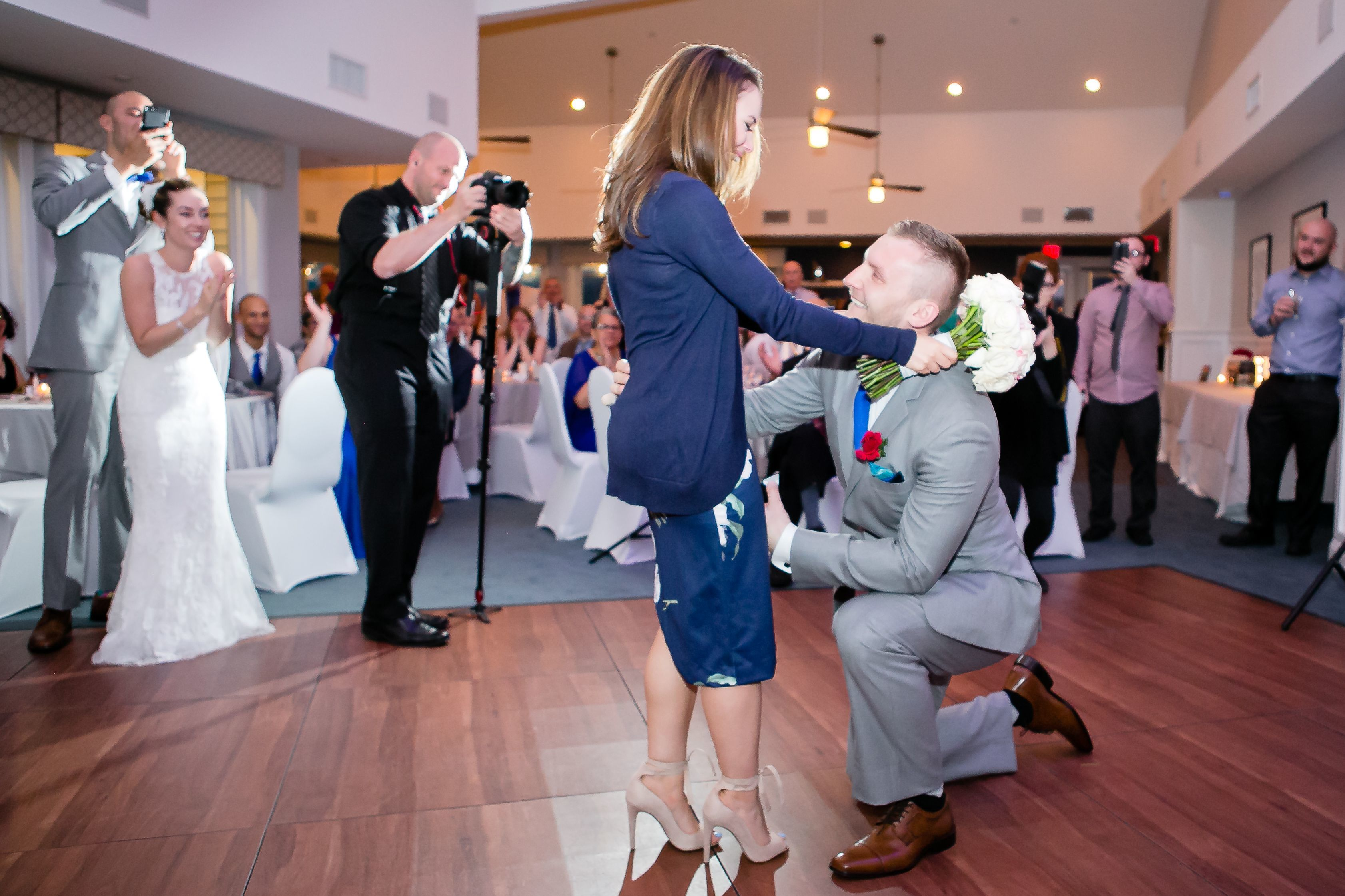 Rather than toss her bouquet, the bride handed it to friend of the couple, Lena. The bride stepped aside, and there was John, the grooms police partner, who proposed.