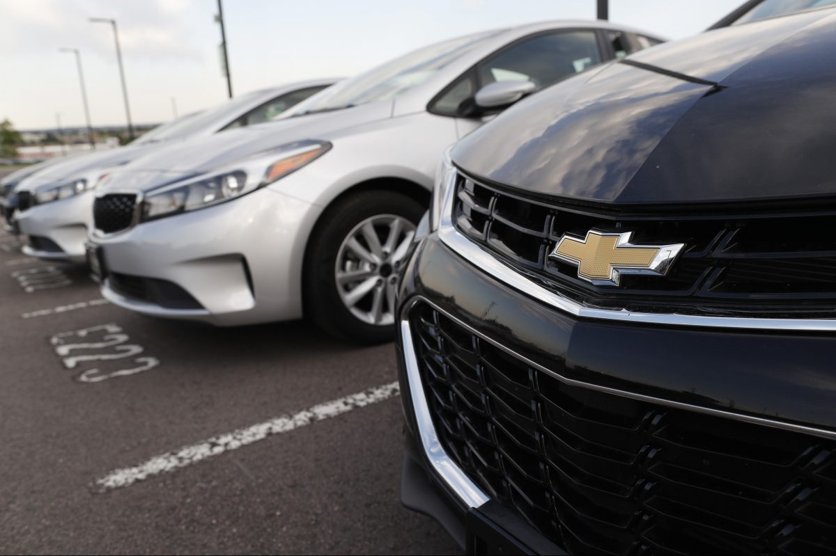 A used 2017 Chevrolet Cruze sits in a row of used, Kia Forte sedans at a dealership in Centennial, Colo.