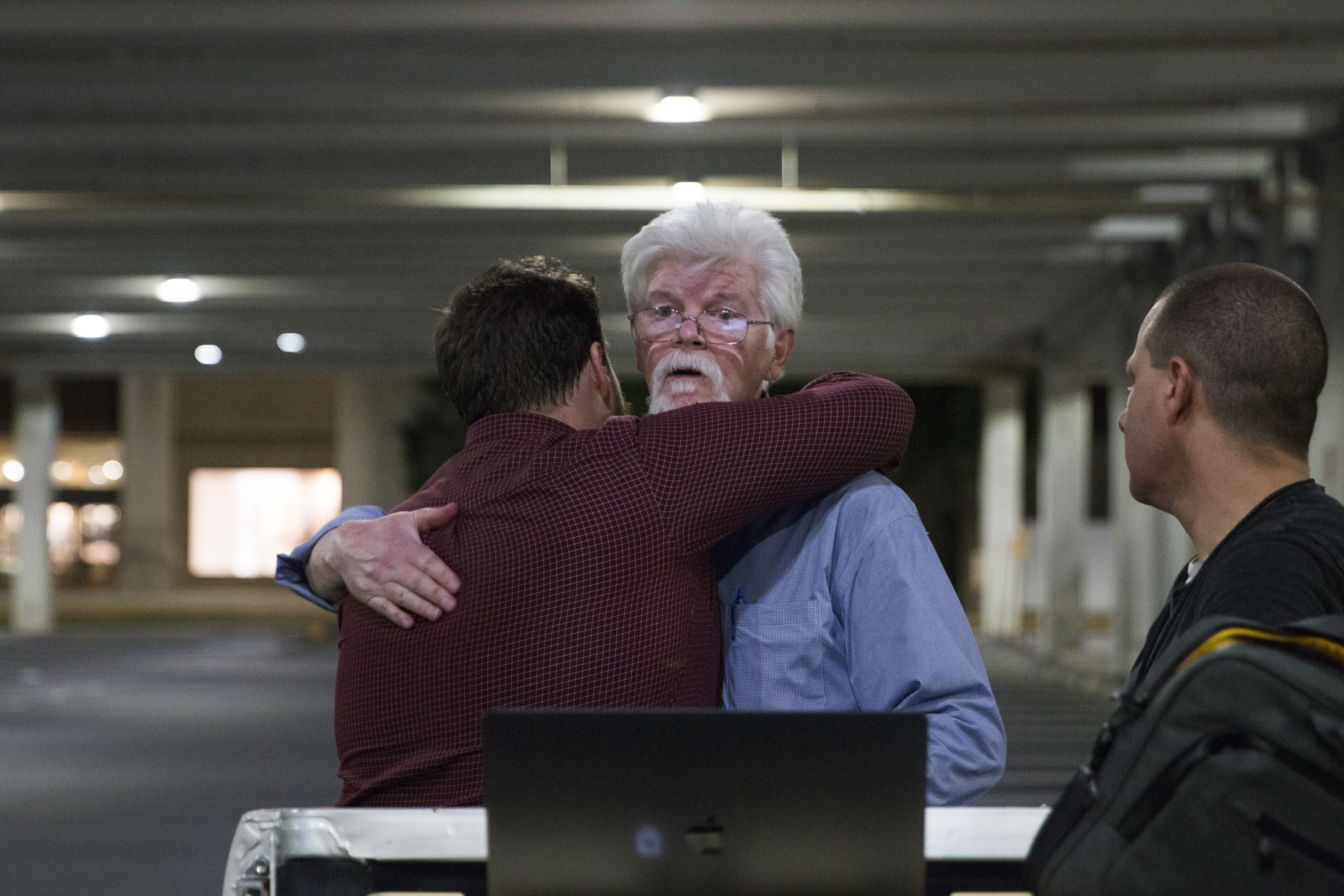 In this Thursday, June 28, 2018 photo, The Capital Gazette reporters Pat Furgurson, center, and Chase Cook hug at a makeshift office in a parking garage of a mall in Annapolis, Md., during coverage of the fatal shootings that happened in their paper´s newsroom earlier in the day.