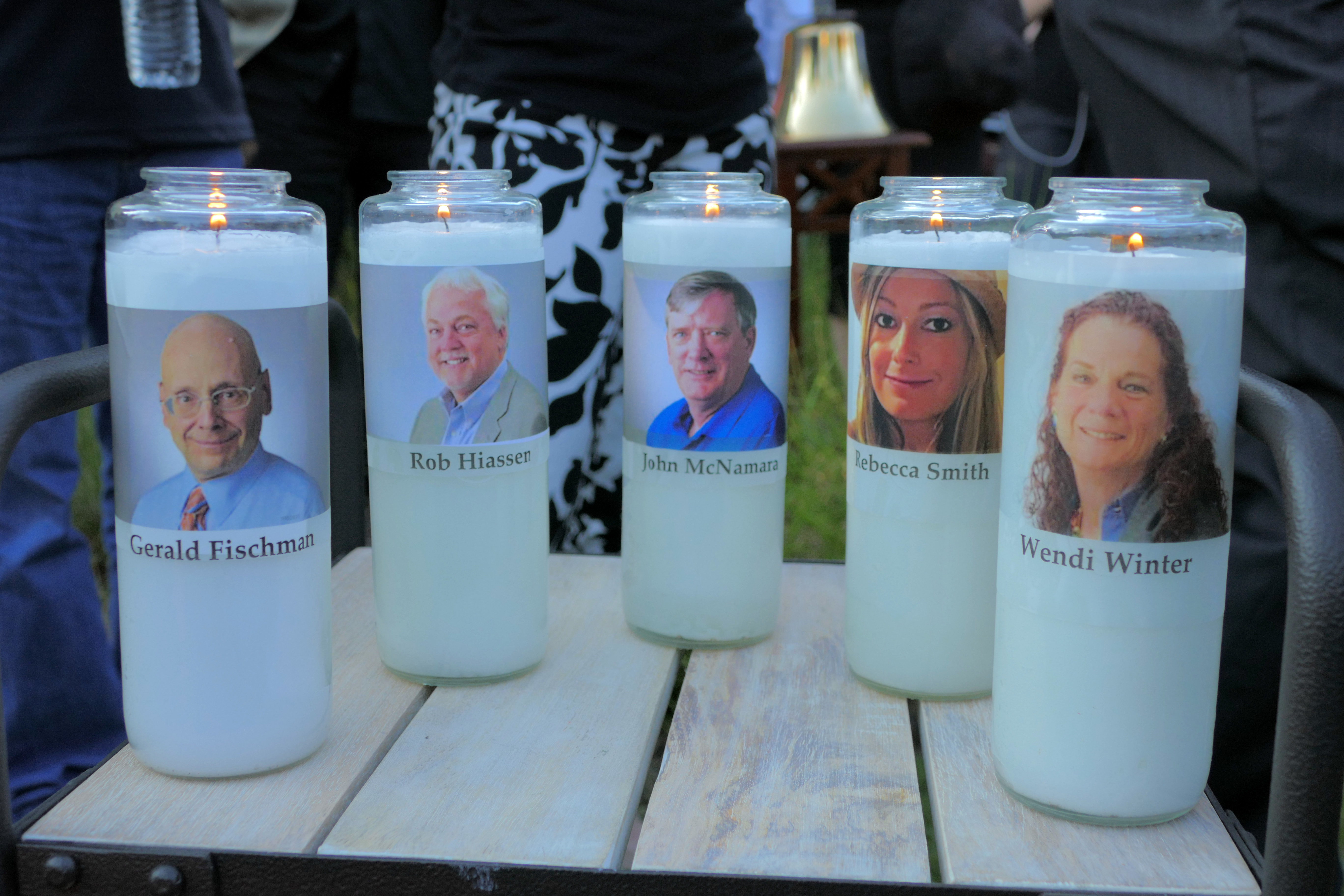 Candles honoring Gerald Fischman, Rob Hiassen, John McNamara, Rebecca Smith, and Wendi Winters flicker as the sun sets during a candlelight vigil on Friday, June 29, 2018, at Annapolis Mall for the five Capital Gazette employees slain during a shooting spree in their newsroom.