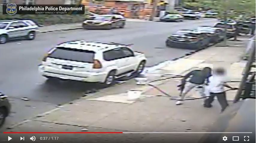 An image from a surveillance video showing a man with an AK-47 assault-style rifle approaching Mike Poeng outside of his West Philadelphia beer deli owner on Saturday, May 5, 2018.