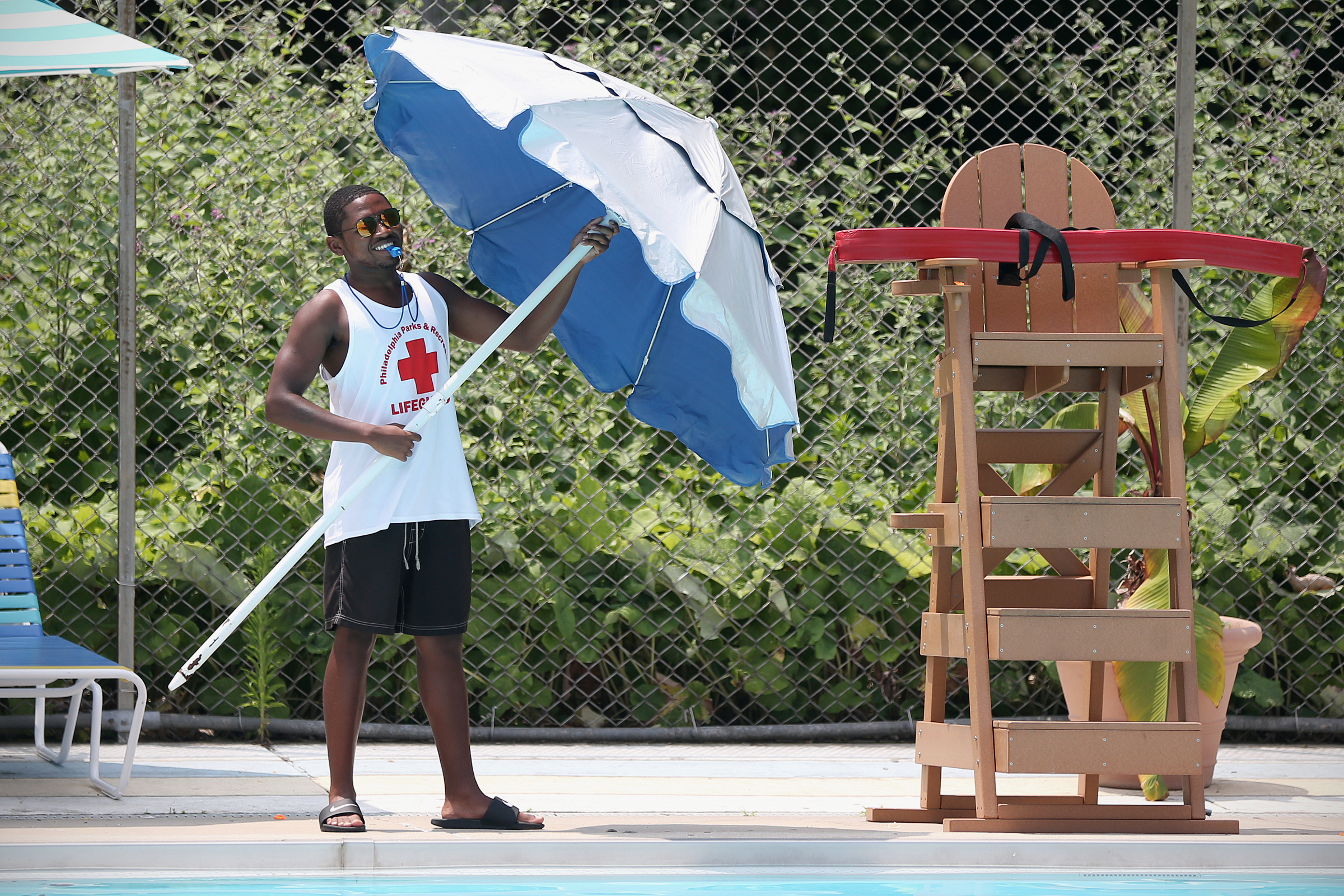Lifeguard Hosni Knox, 18, opens an umbrella at the Lee Cultural Center pool in West Philadelphia on Tuesday July 3, 2018.