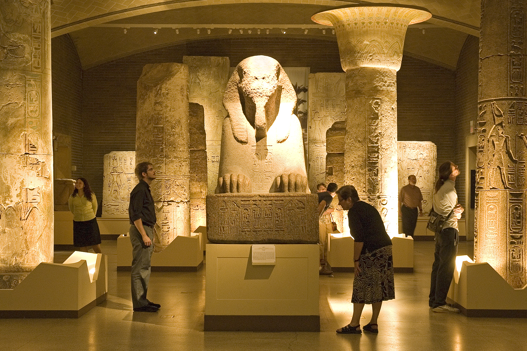 Visitors to the Penn Museum explore the Egyptian gallery and its centerpiece, the Sphinx of Ramesses II from Memphis, Egypt—the sixth-largest granite sphinx in the world, and the largest in the western hemisphere. The gallery is closing for several years of renovations, conservation, and reinstallation. Photo by Lauren Hansen-Flaschen.