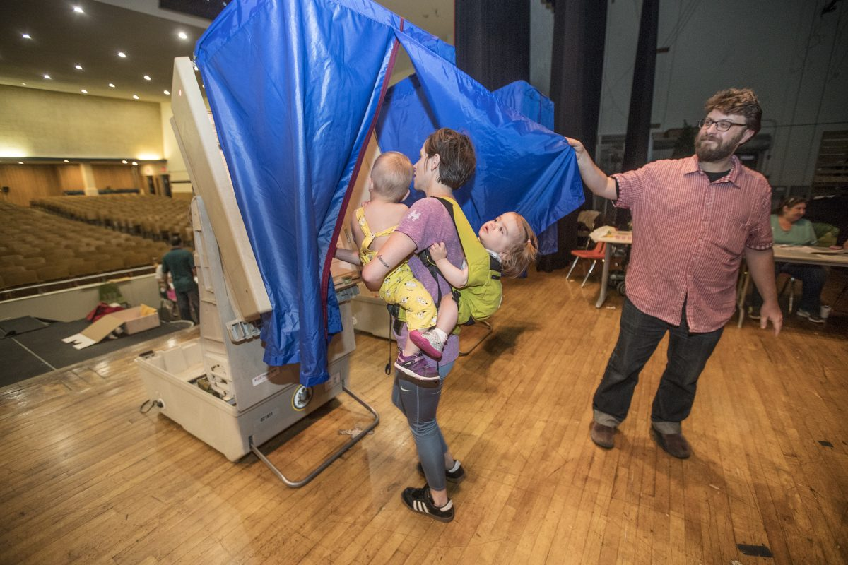 Vera Dugan, 18 months, right, holds on tight to Bridget Huffman, center, who holds her son Drew Huffman, 20 months, left, as they all go into the voting booth on the stage of the auditorium of South Philadelphia High School on May 15, 2018. Nazim Karacaa, right, holds open the blue curtain so Huffman and her brood can enter to vote in the primary election in the 39th District in South Philadelphia.