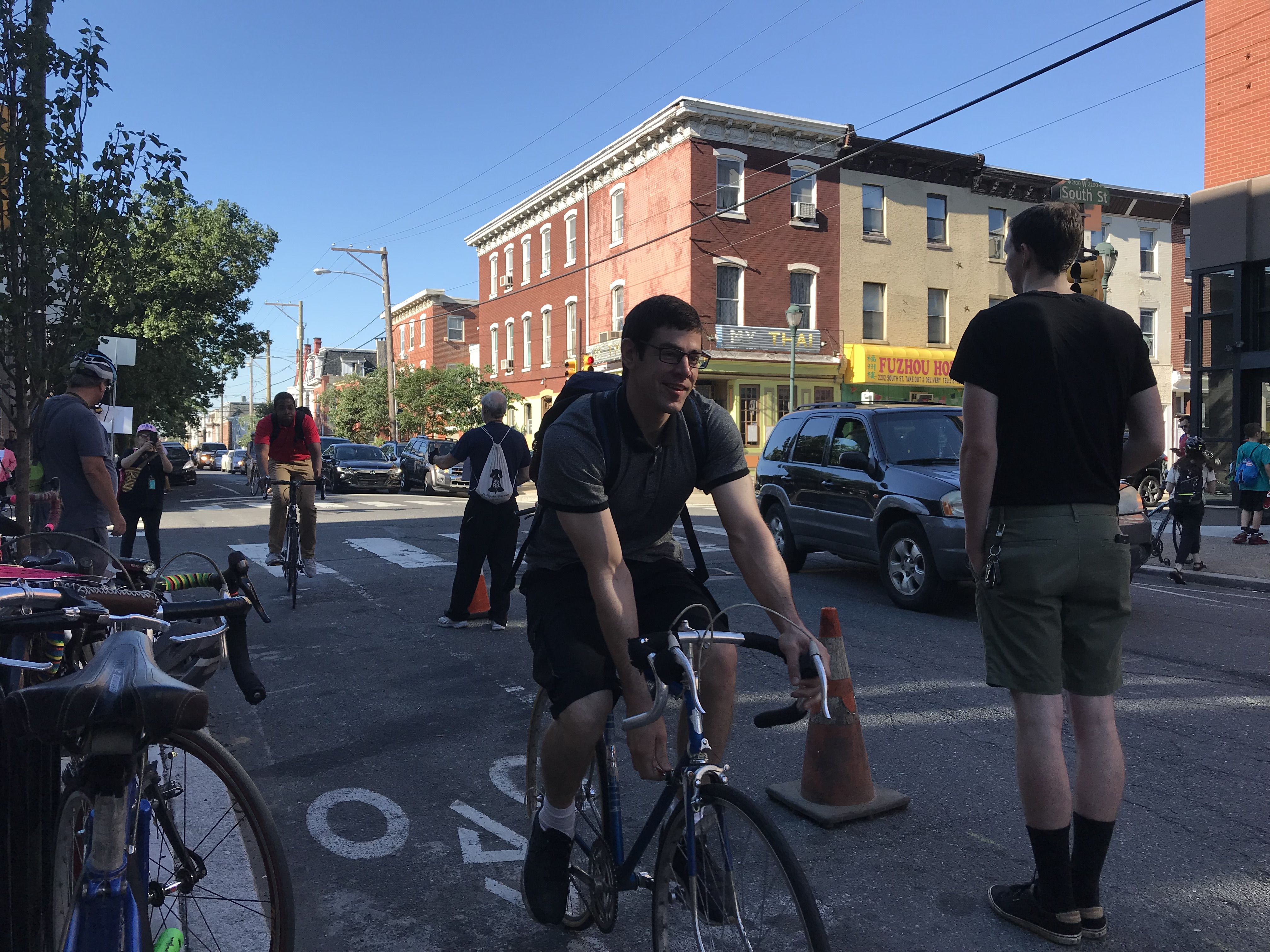 Cyclists pass demonstrators who lined the bike lane on 22nd Street between South and Lombard to draw attention to the poor condition of the street.