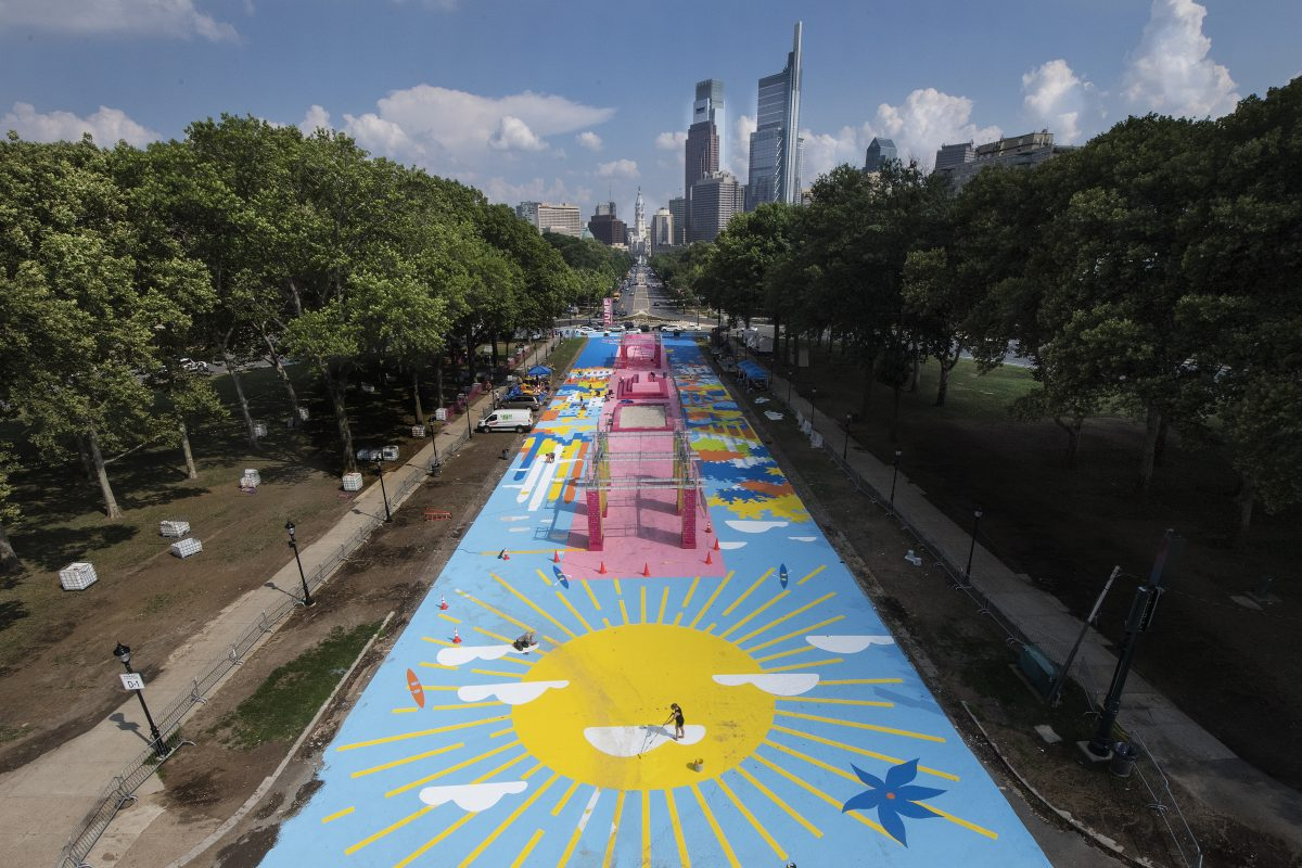 Artist Elise Stewart paints the sun on a ground mural painted for this year's pop-up urban beach, near Eakins Oval in Philadelphia, Pa. Monday, July 16, 2018. JOSE F. MORENO / Staff Photographer