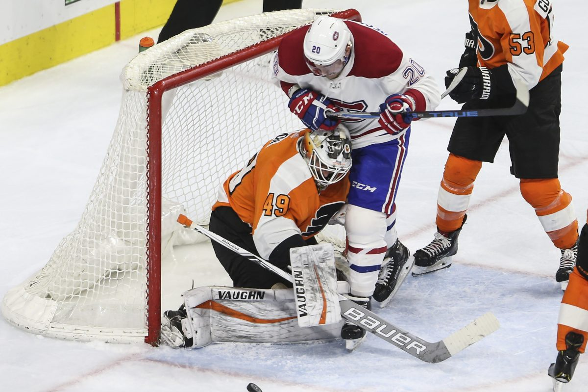 Flyers goalie Alex Lyon stops the puck with the Canadiens' Nicolas Deslauriers bumping him during a Feb. 20 game last season.