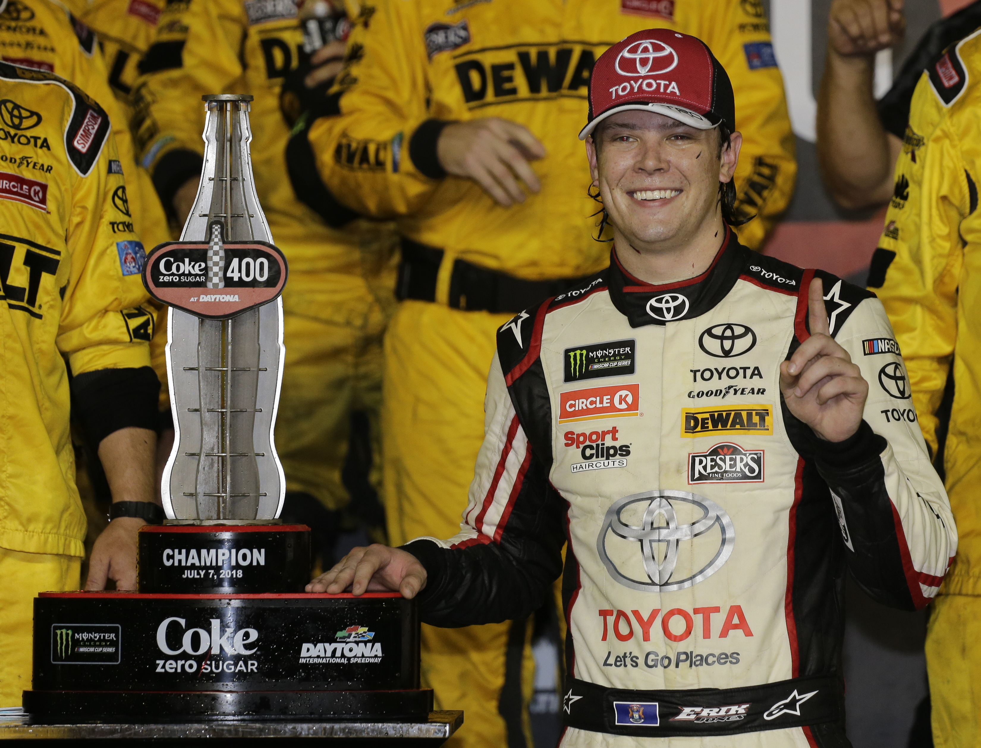 Erik Jones smiles next to the trophy after winning the NASCAR Cup Series auto race at Daytona International Speedway, Saturday, July 7, 2018, in Daytona Beach, Fla. (AP Photo/Terry Renna)